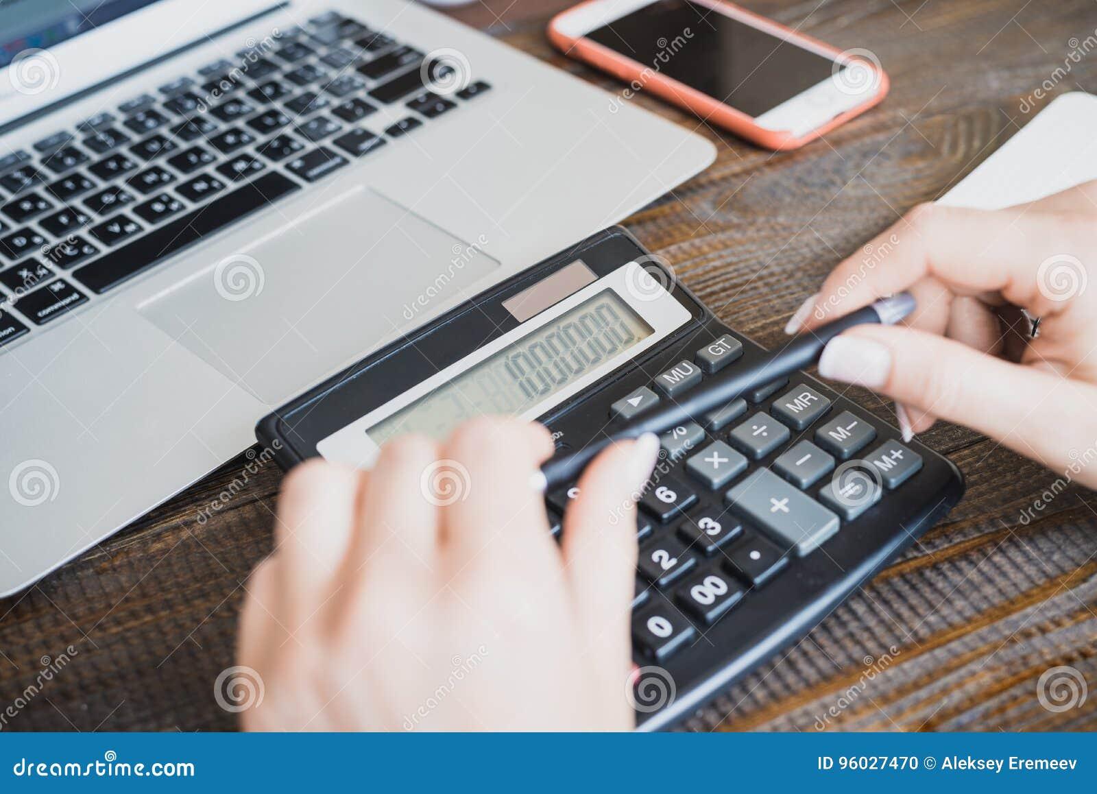 Ranku biznesu dama Kobiet ręki z piórem i kalkulatorem, na którym liczy milion Tło jest smartphone i