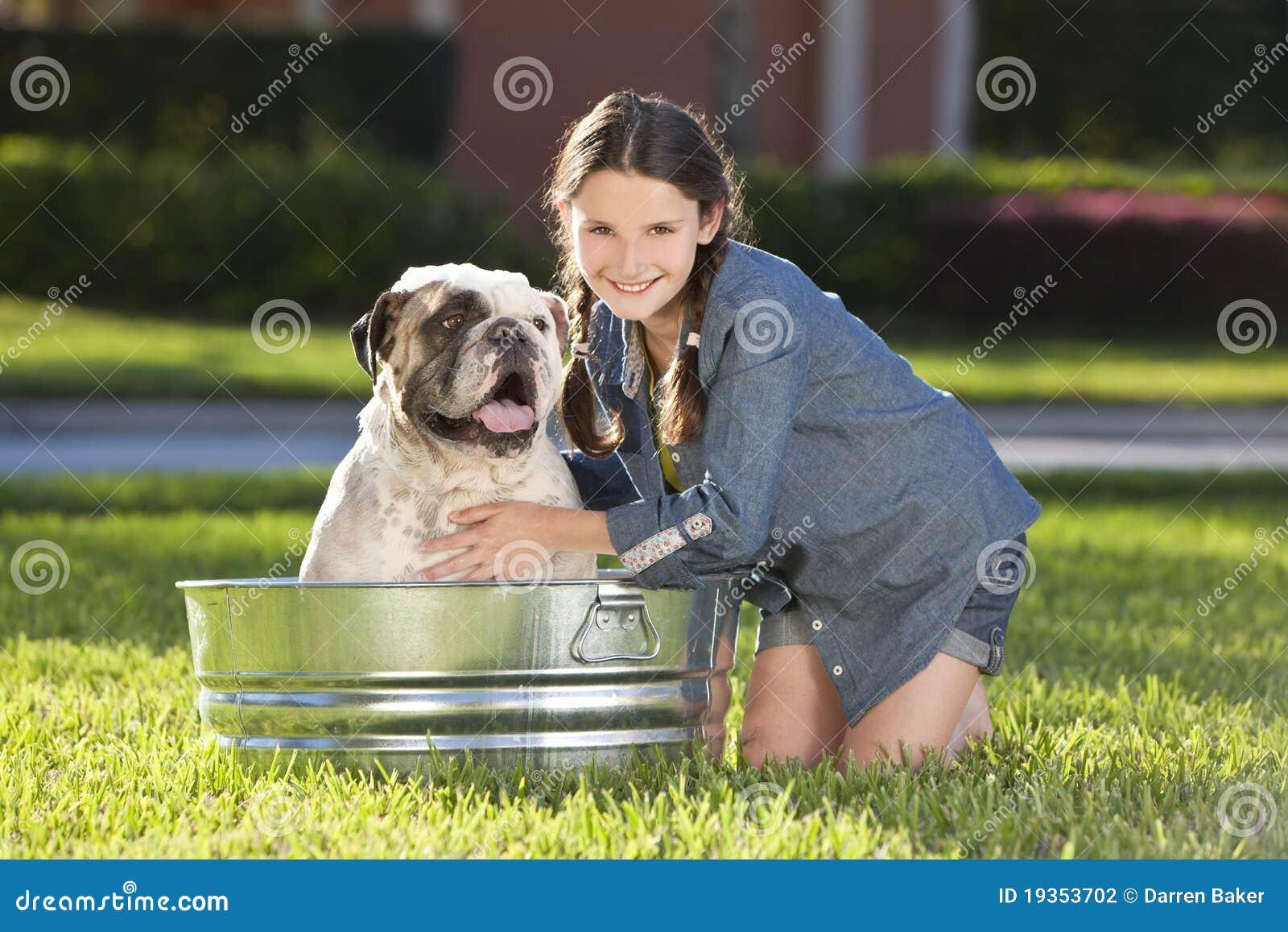 Rapariga bonita que lava seu cão de animal de estimação em uma cuba