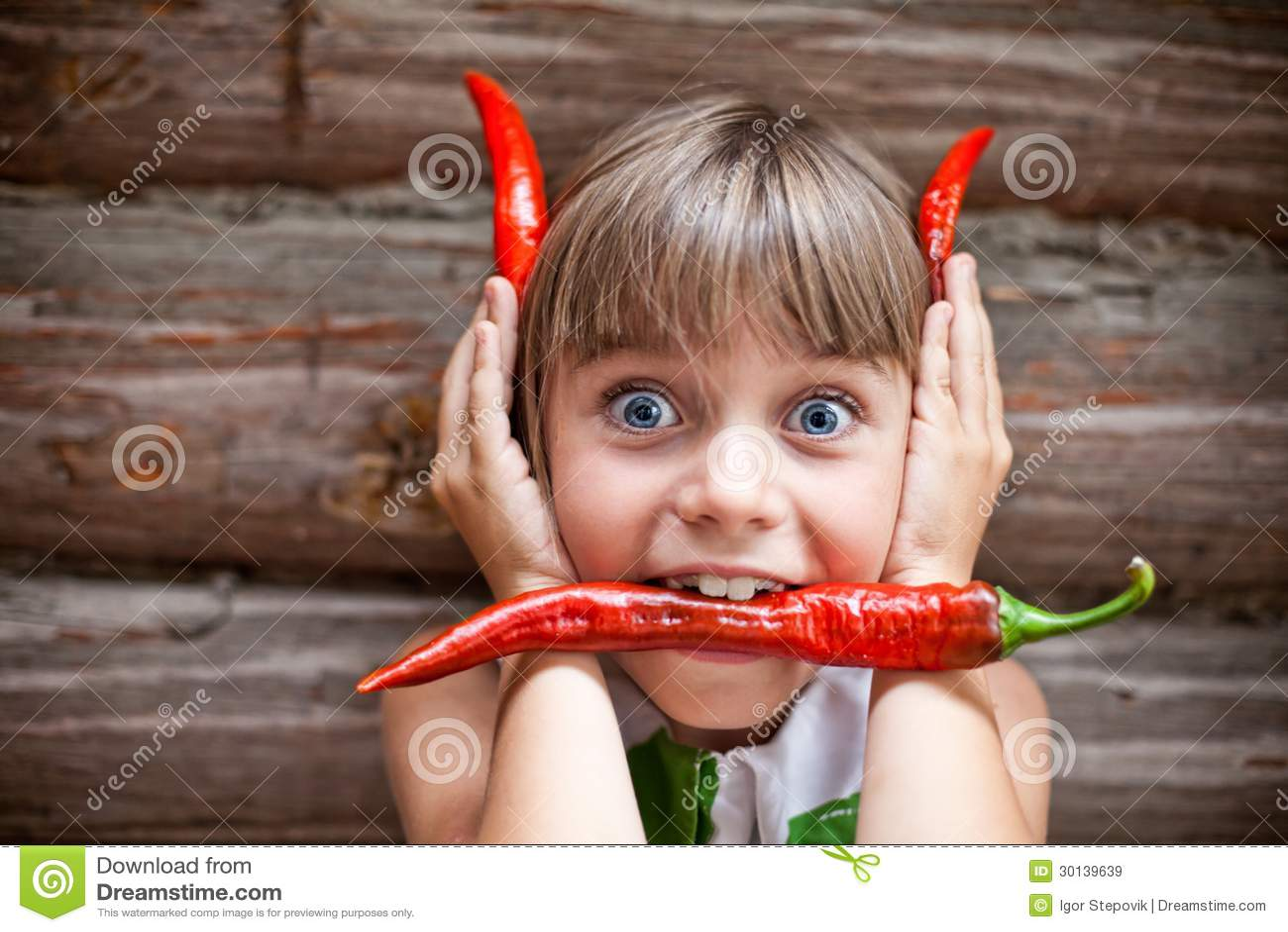Menina com uma pimenta de pimentão encarnado em seus chifres do diabo da mostra da boca