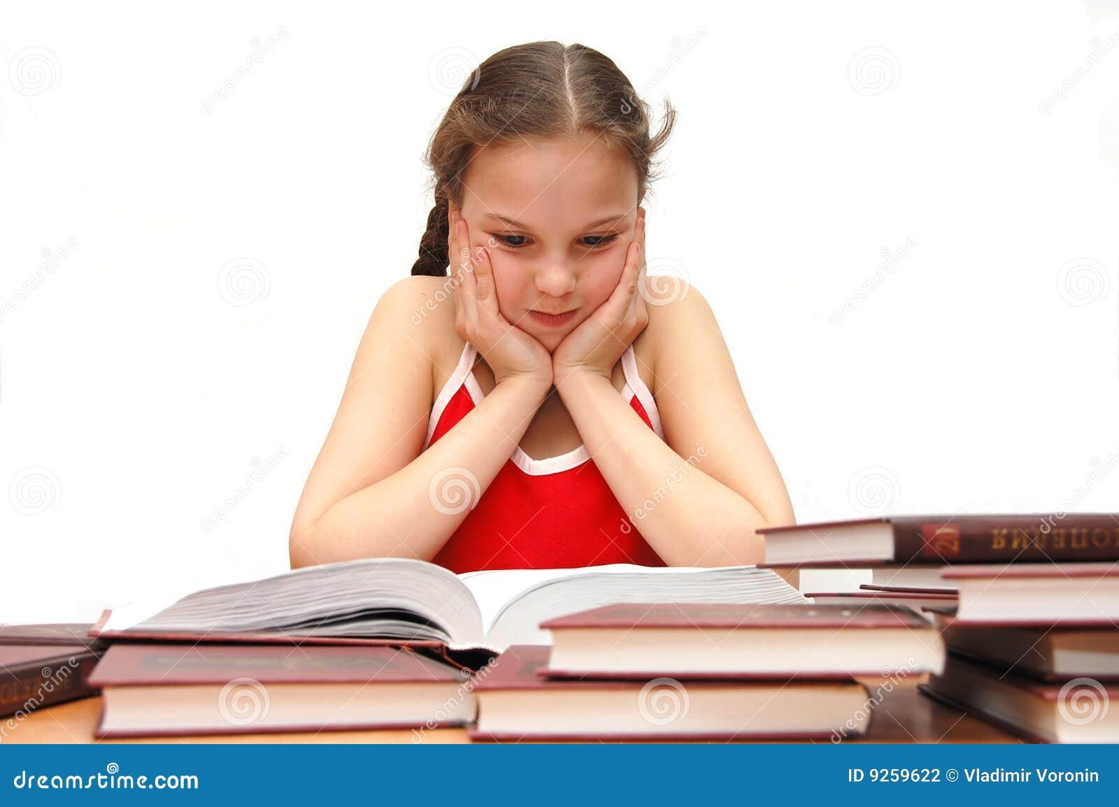 A rapariga o adolescente lê livros