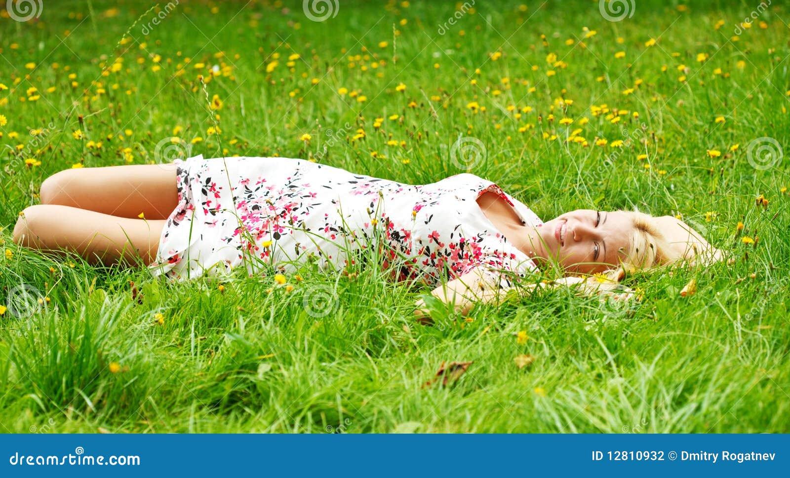 Rapariga que relaxa em um prado