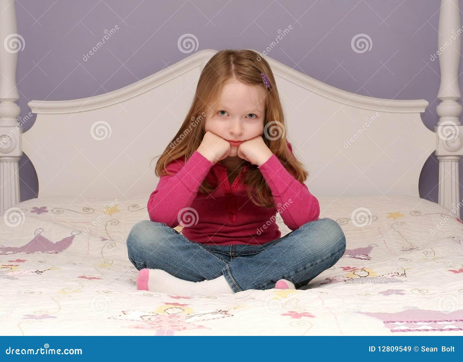 Rapariga que senta-se na cama