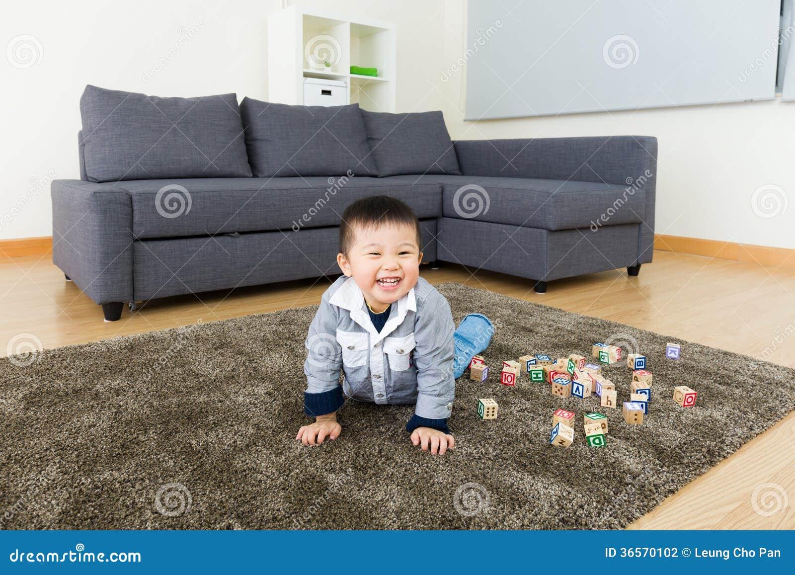 Rapaz pequeno asiático que joga o bloco do brinquedo