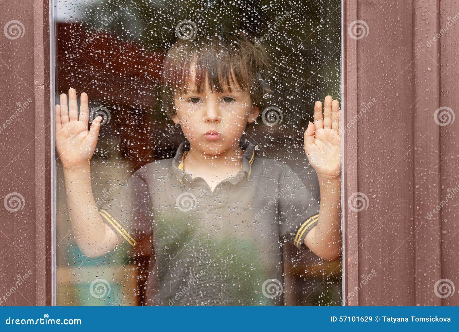 Rapaz pequeno atrás da janela na chuva