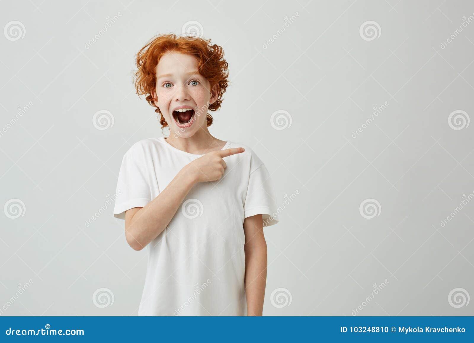 Rapaz pequeno bonito alegre com cabelo encaracolado do gengibre e sardas sorriso feliz e apontar de lado com o dedo no branco