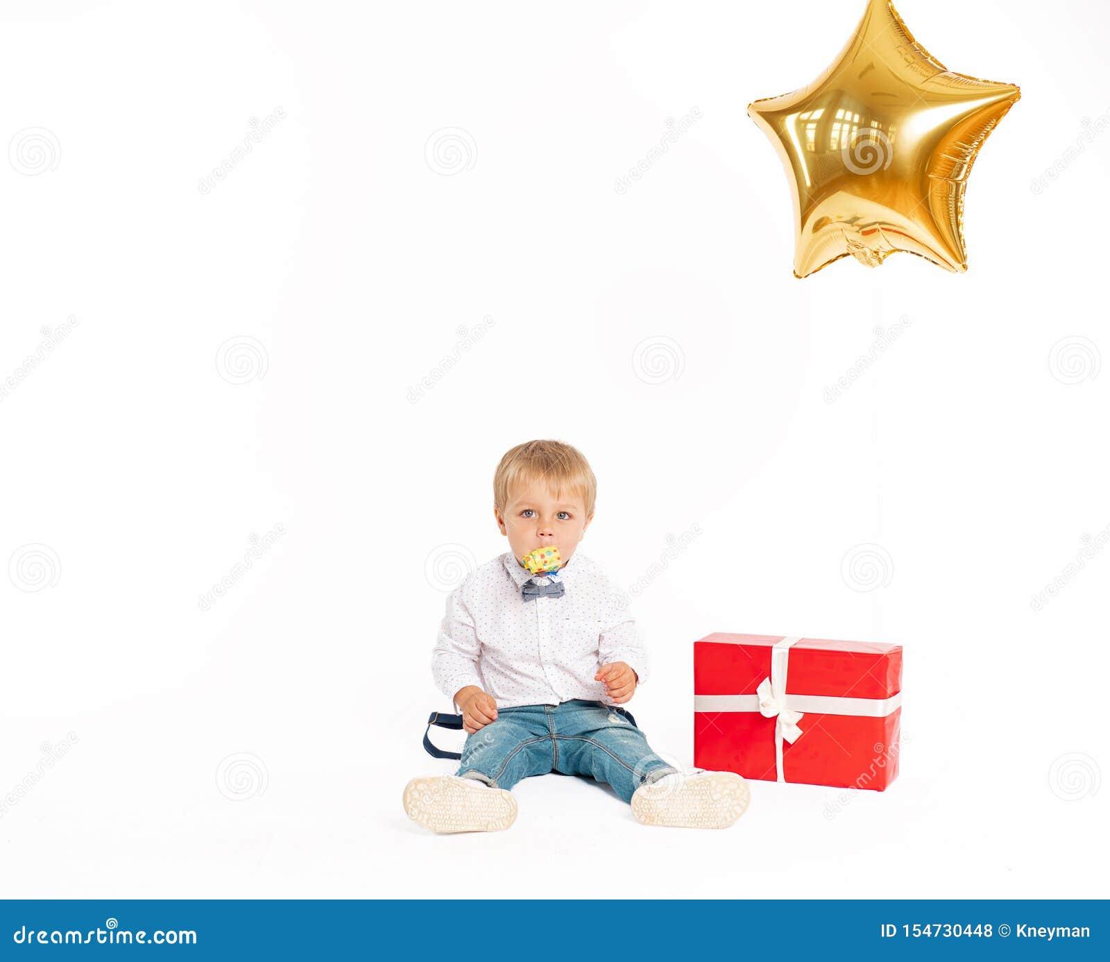Rapaz pequeno bonito, calças de brim e camisa, estando perto do presente e fundindo no acordo do aniversário