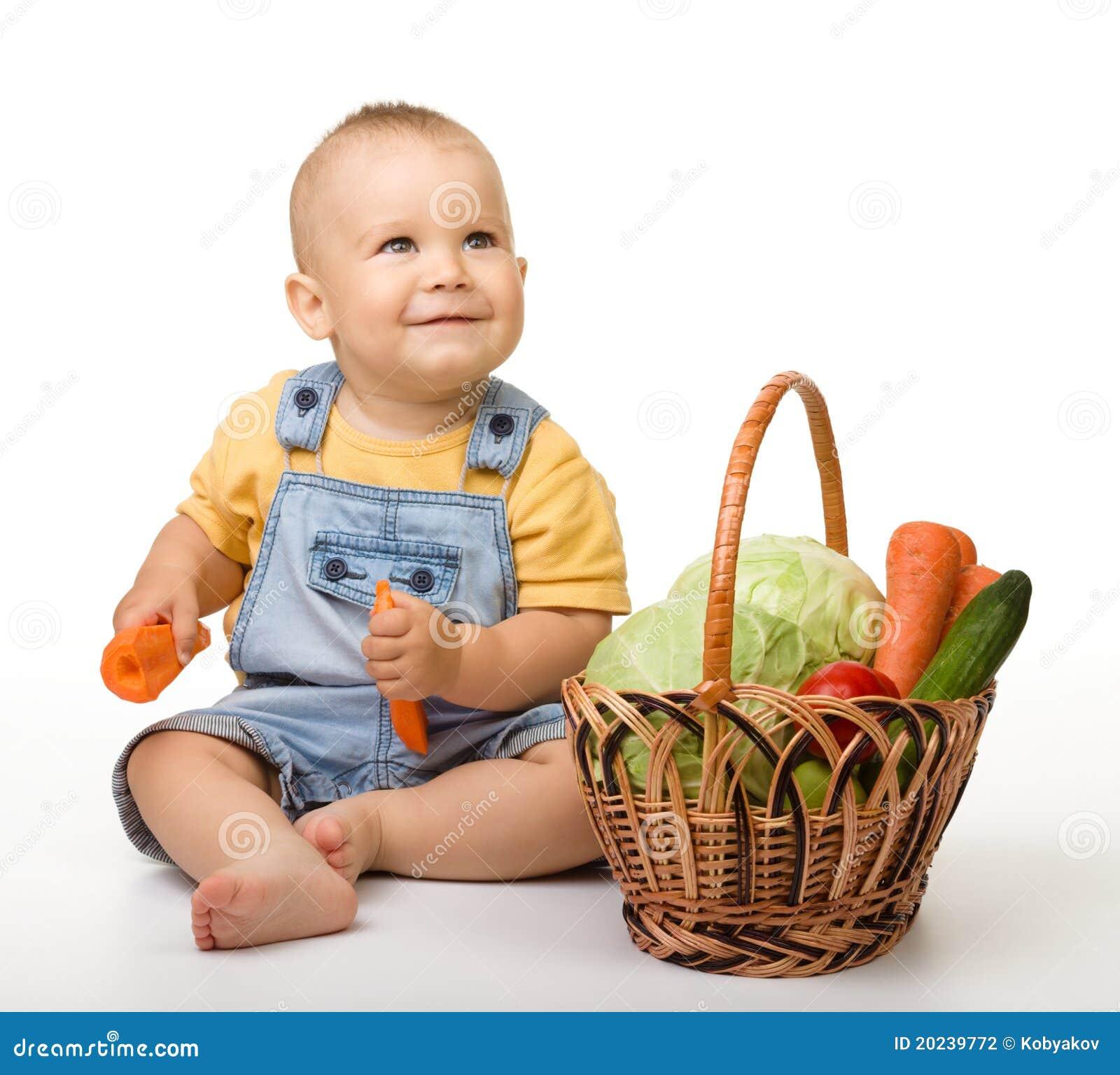 Rapaz pequeno bonito com a cesta cheia dos vegetais