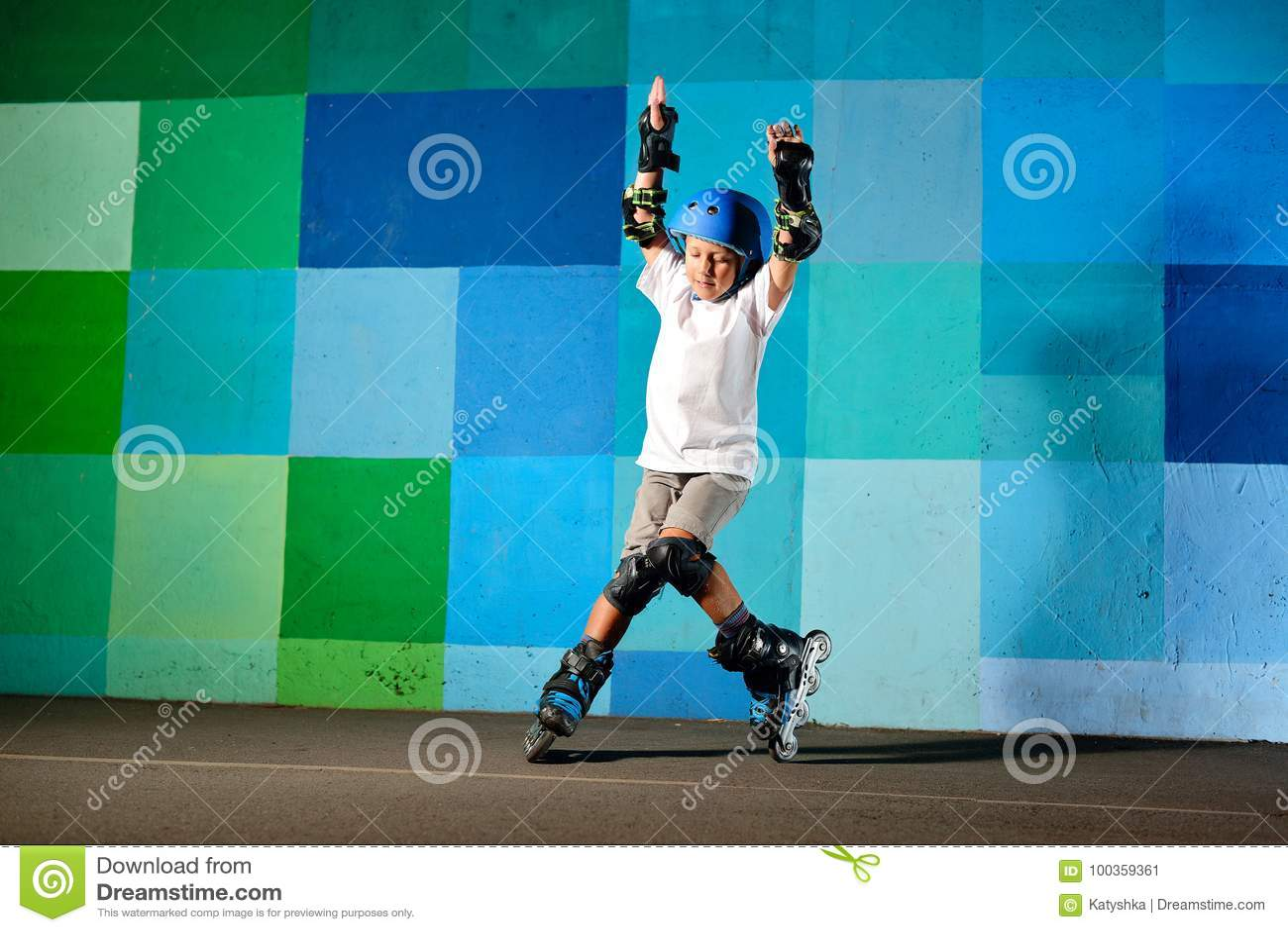 Rapaz pequeno bonito nos patins de rolo que correm contra a parede azul dos grafittis