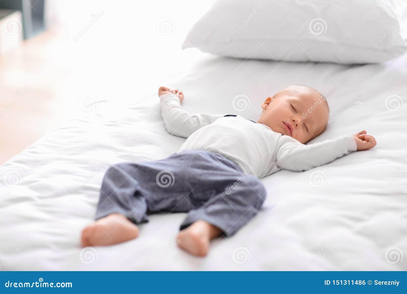Rapaz pequeno bonito que dorme na cama