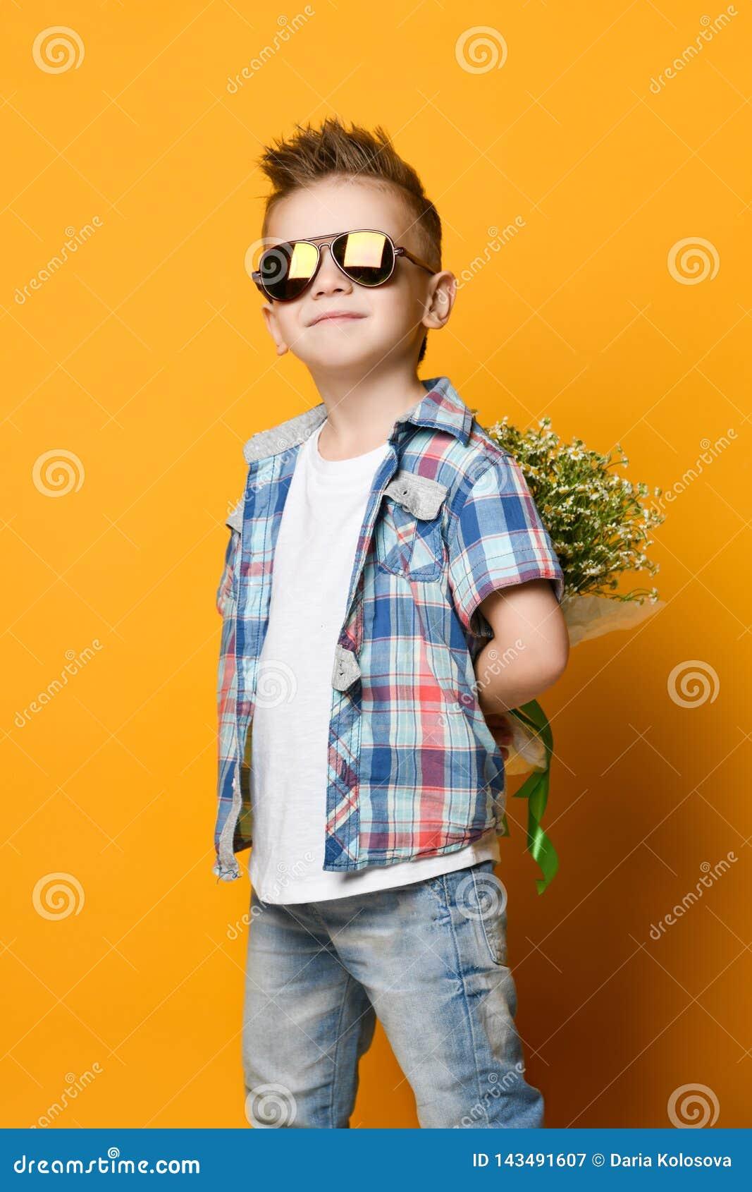 Rapaz pequeno bonito que guarda um ramalhete das flores