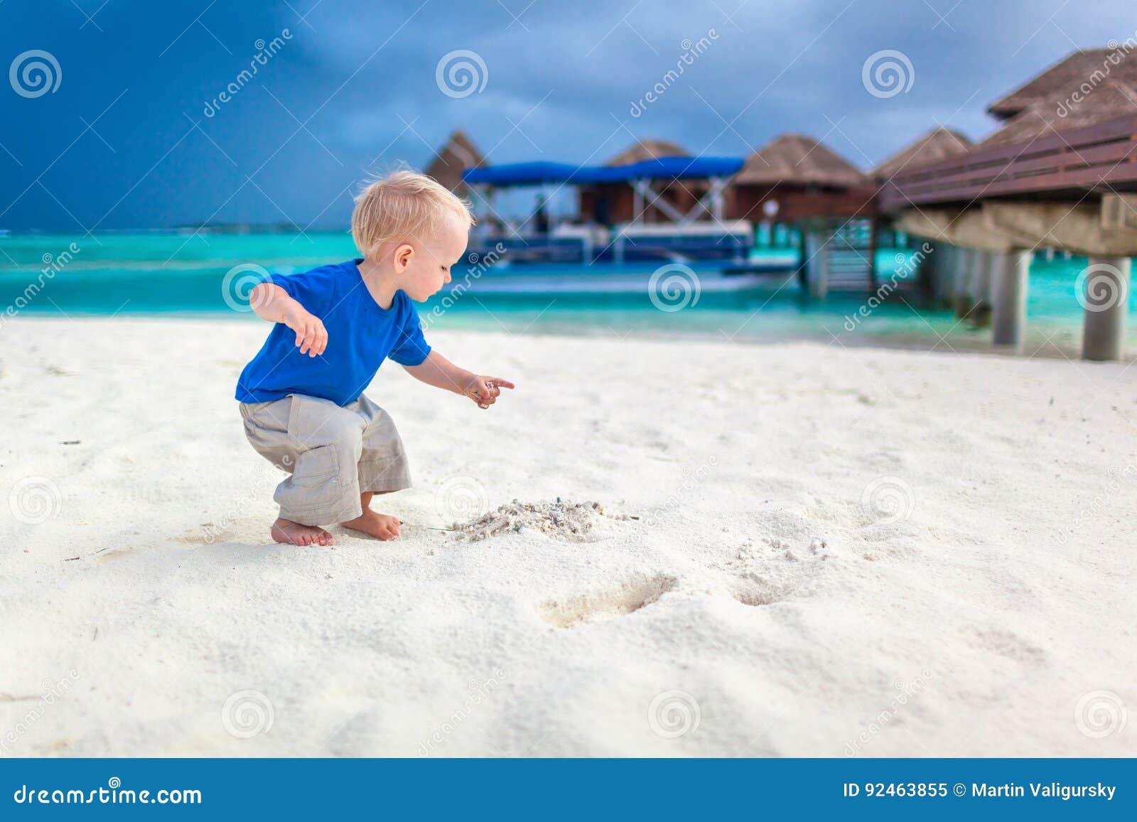 Rapaz pequeno bonito que procura o tesouro na praia tropical