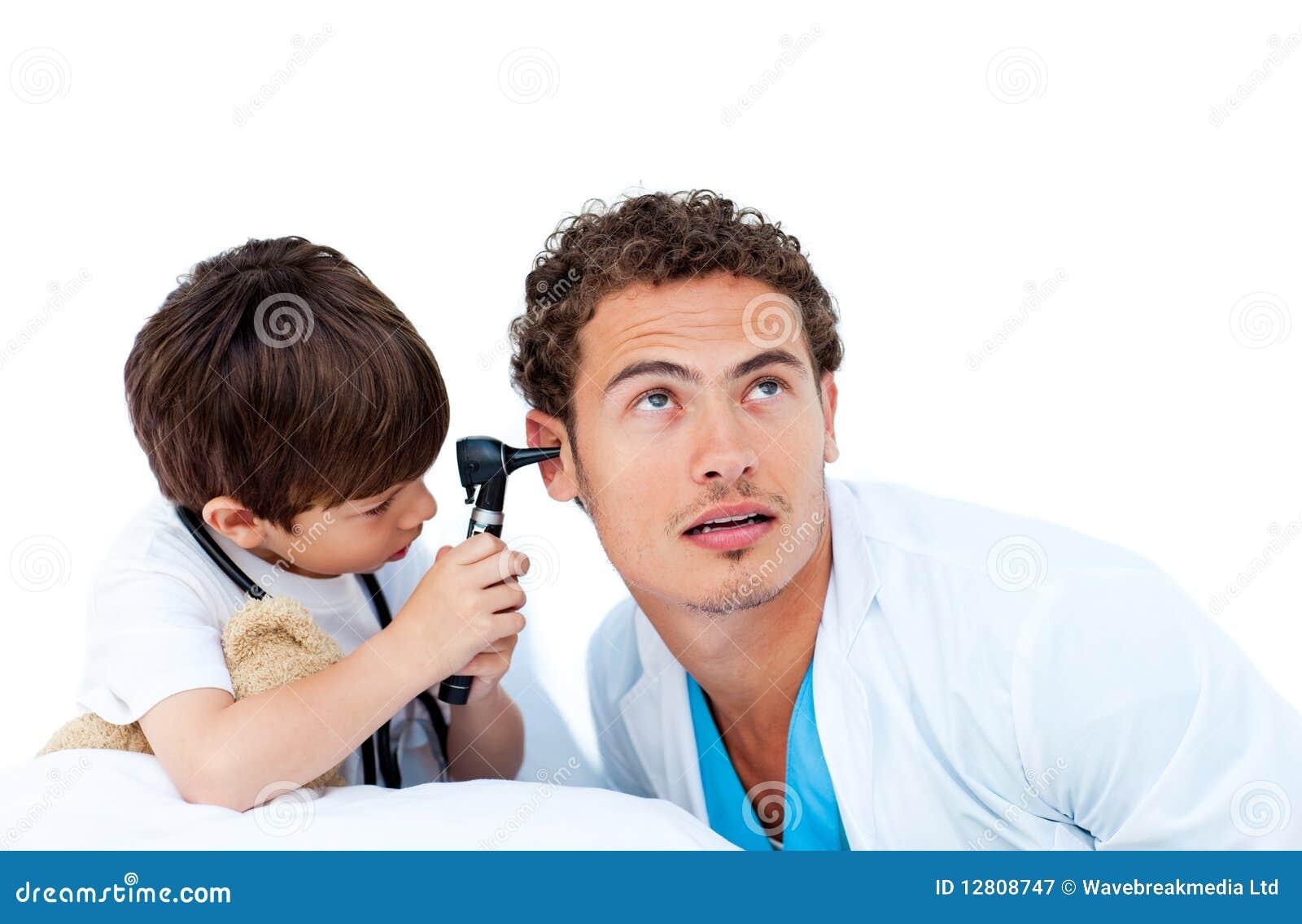 Rapaz pequeno bonito que verific as orelhas do doutor