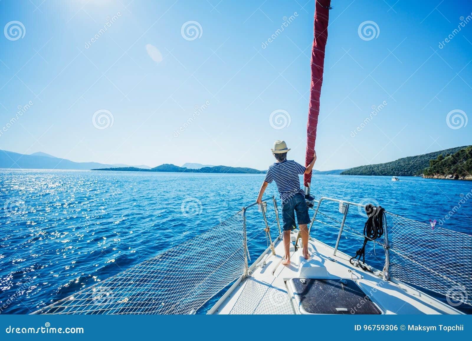 Rapaz pequeno a bordo do iate da navigação no cruzeiro do verão Aventura do curso, vela com a criança em férias em família