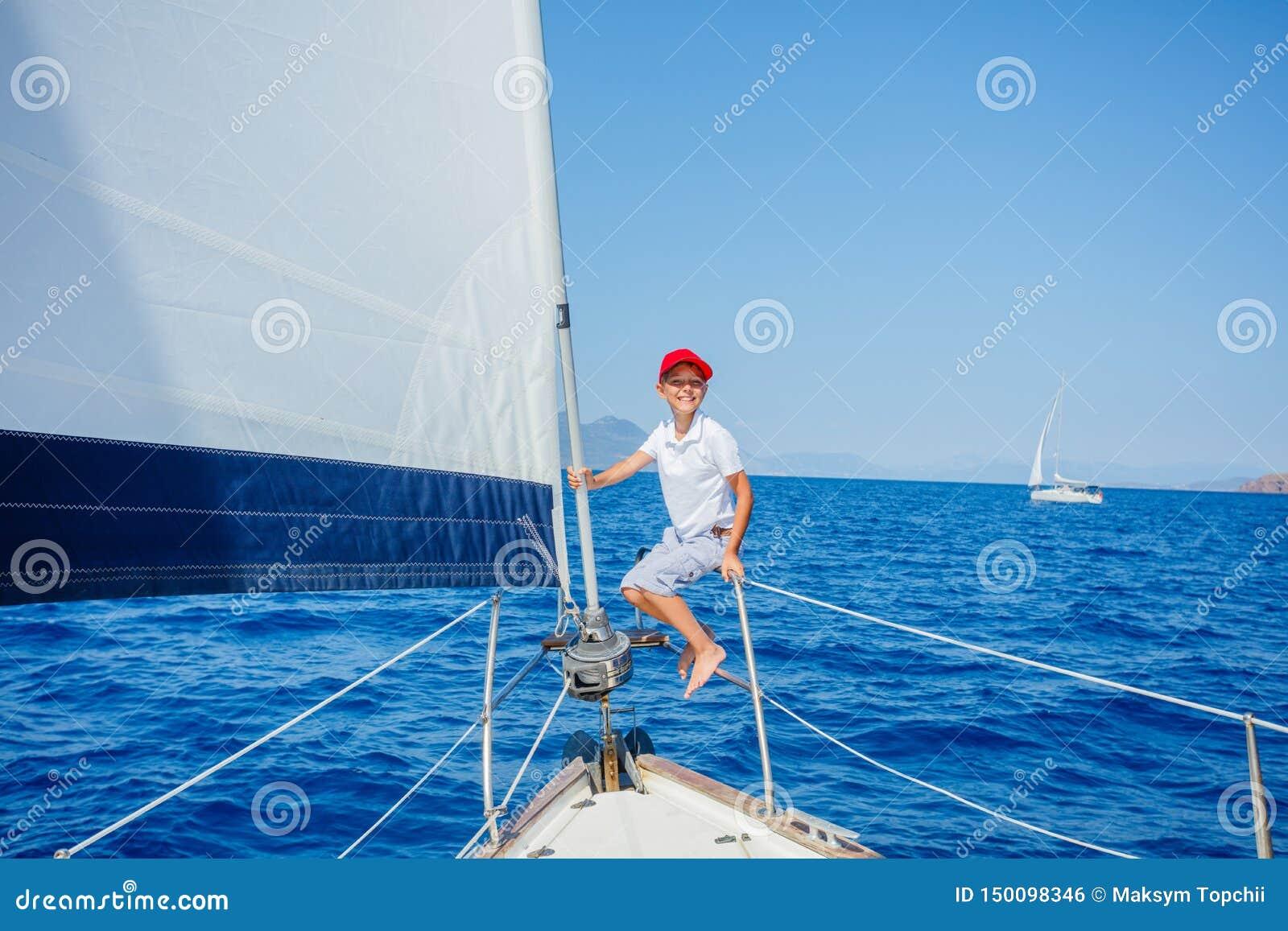 Rapaz pequeno a bordo do iate da naviga??o no cruzeiro do ver?o Aventura do curso, vela com a crian?a em f?rias em fam?lia