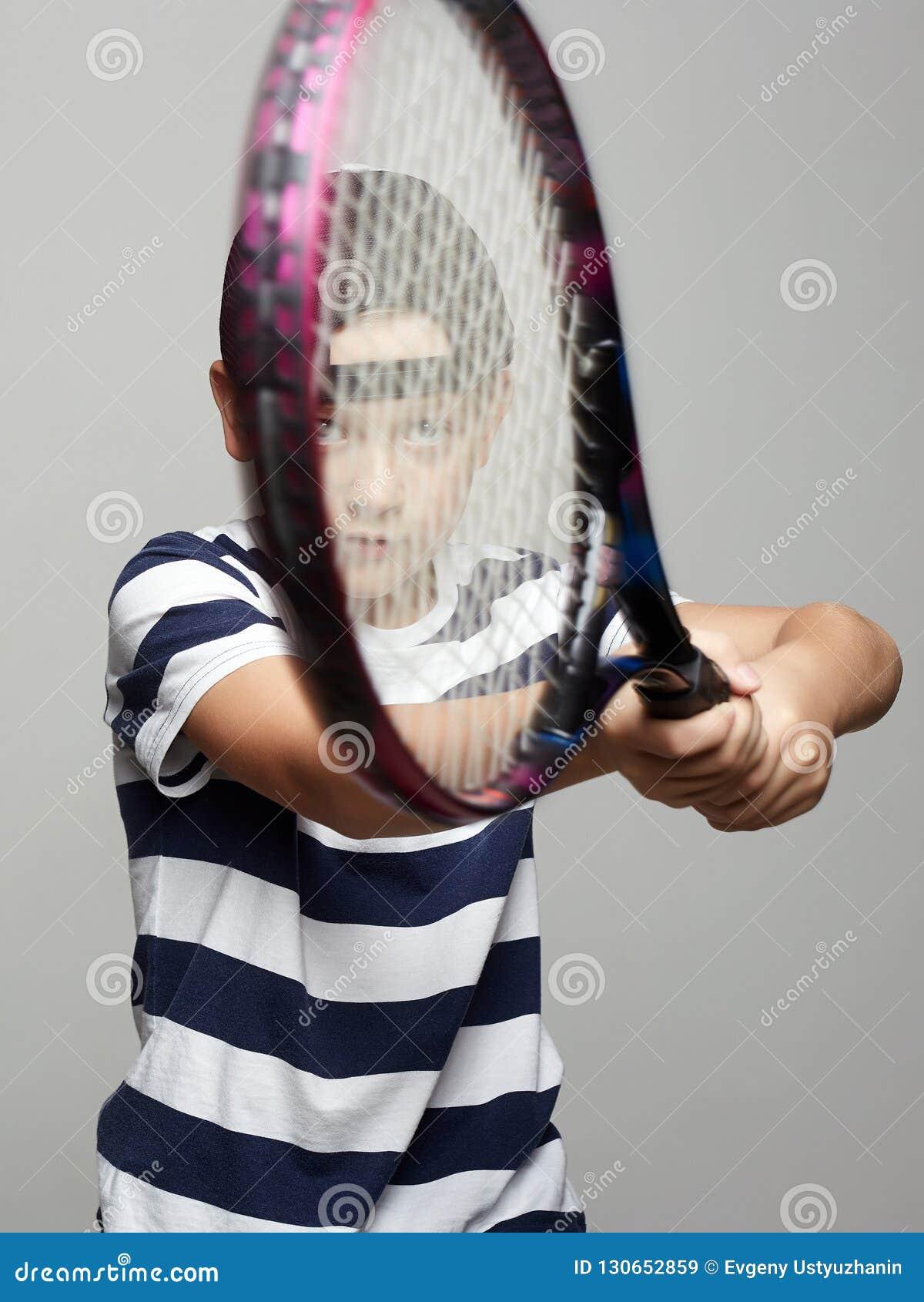 Rapaz pequeno com raquete de tênis