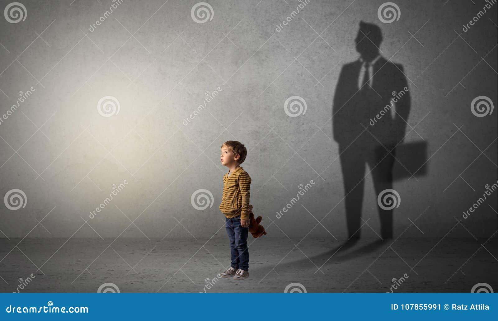 Rapaz pequeno com sombra do homem de negócios