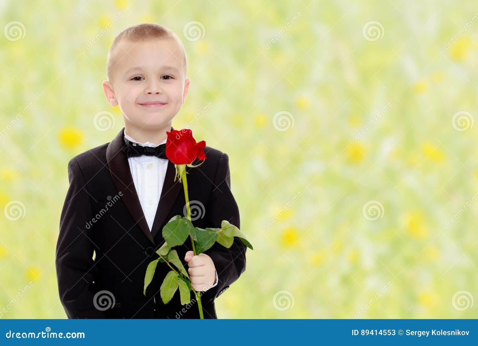 Rapaz pequeno com uma flor da rosa