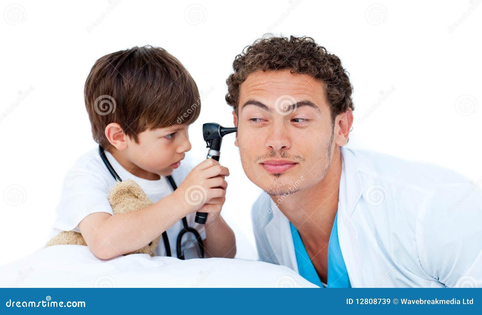 Rapaz pequeno concentrado que joga com o doutor