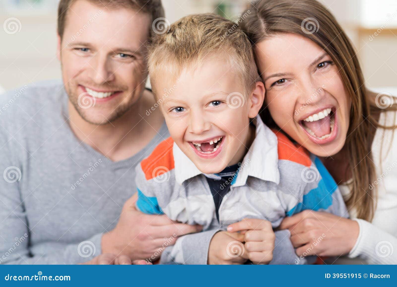 Rapaz pequeno de riso com seus pais novos