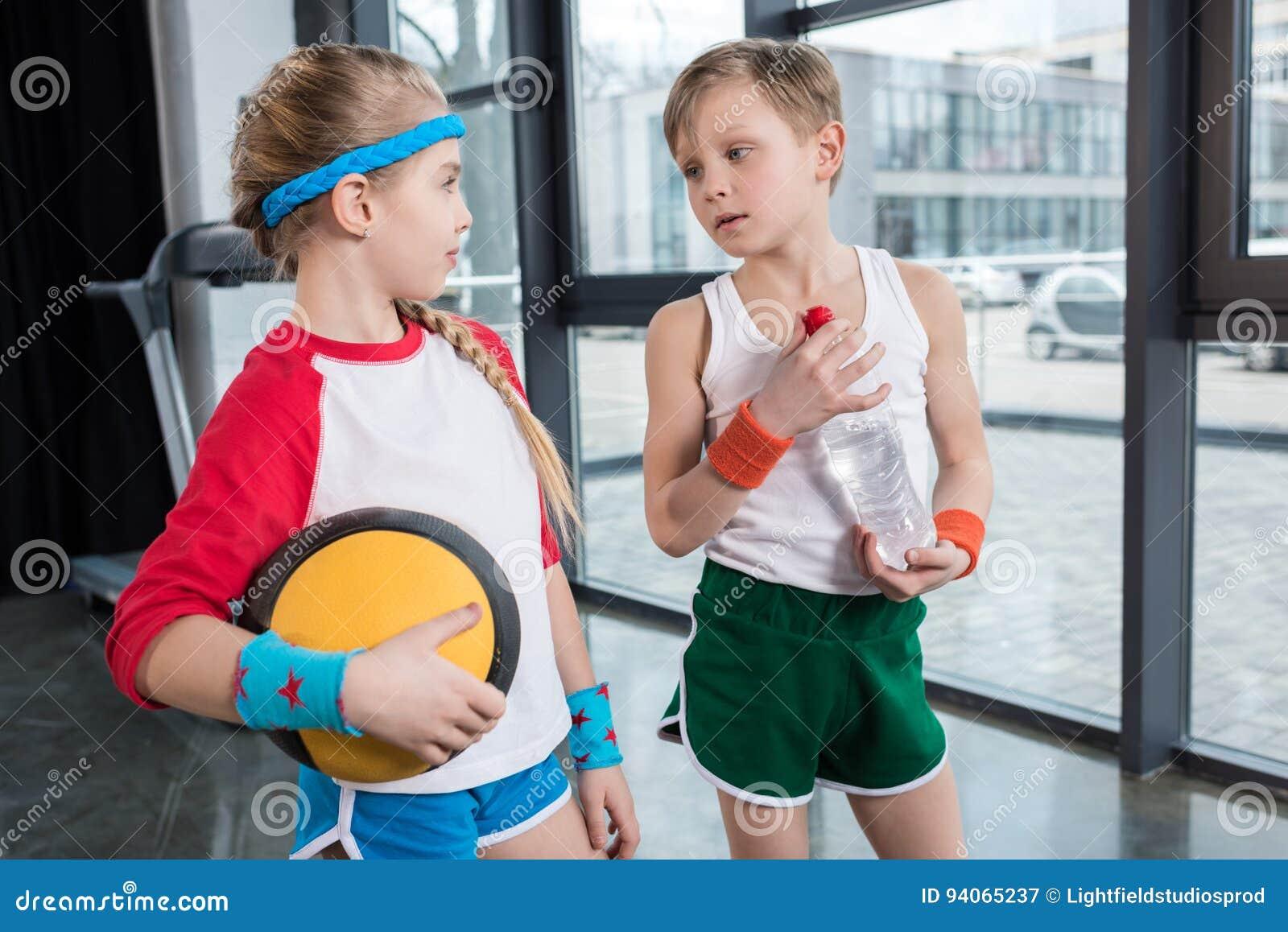 Rapaz pequeno e menina no sportswear que falam no estúdio da aptidão