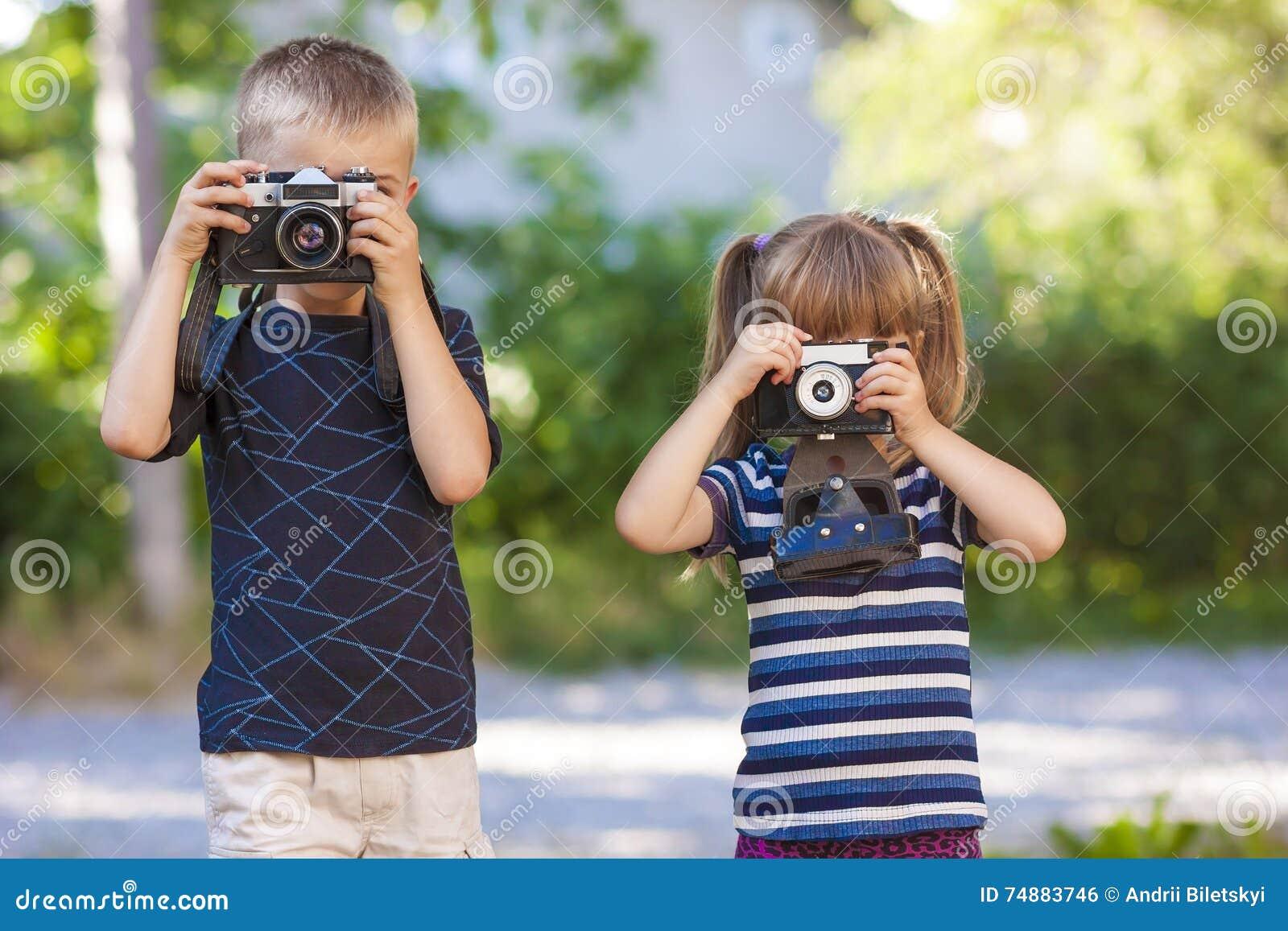 Rapaz pequeno e menina que aprendem como usar a câmera da foto