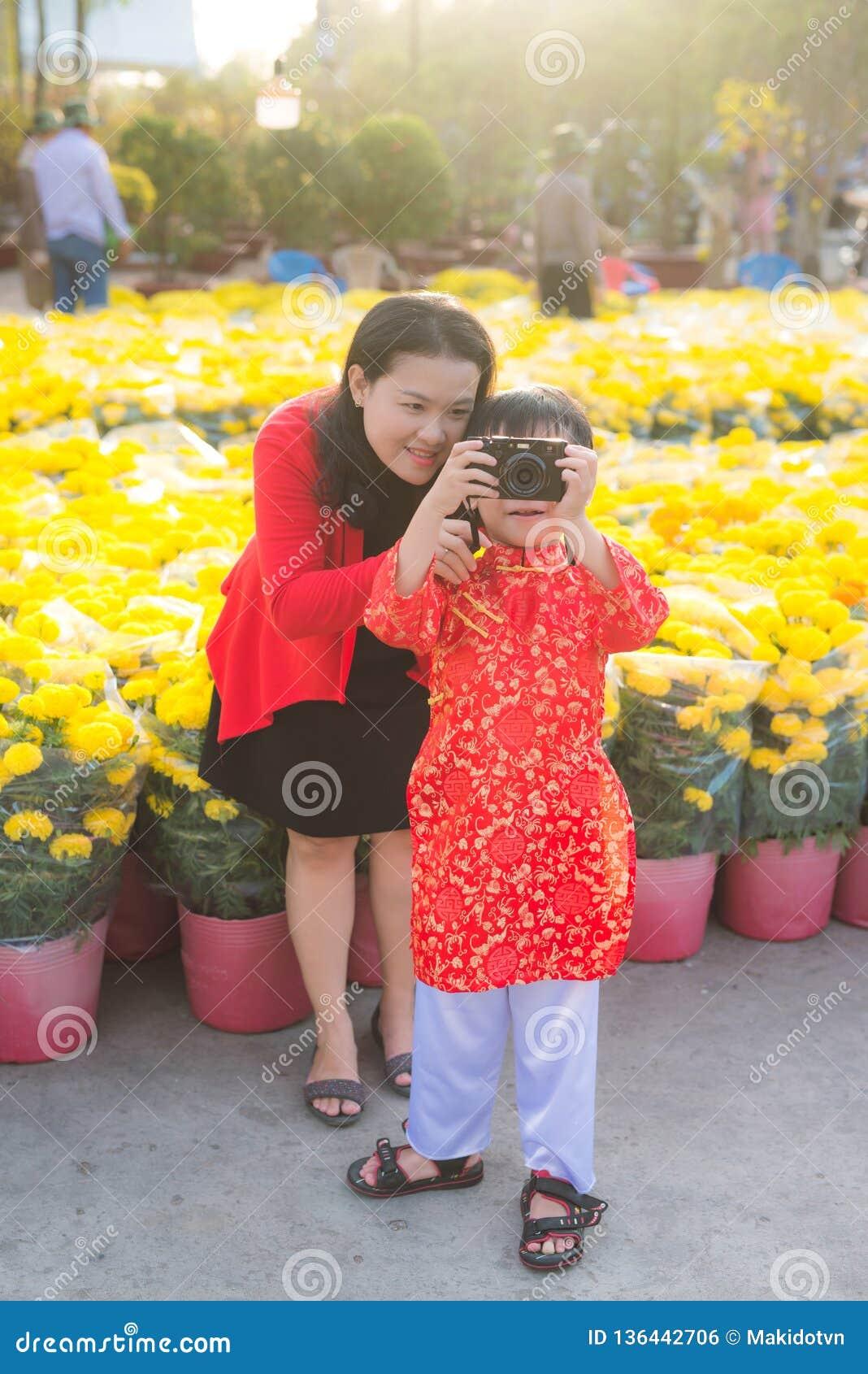 Rapaz pequeno e sua mãe nova bonita que tomam a imagem com a câmera digital da foto Família feliz que faz a foto na flor de Tet
