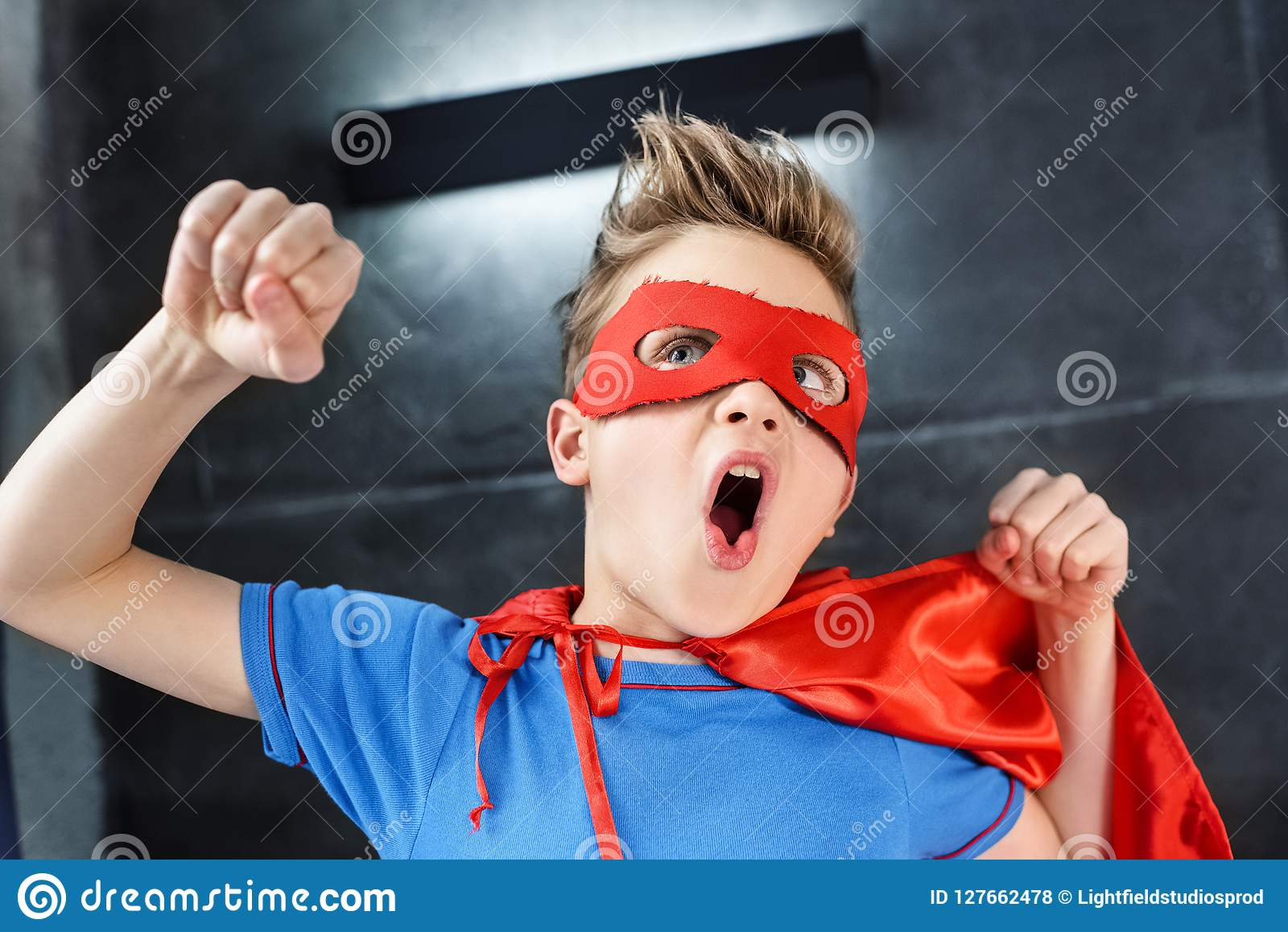 Rapaz pequeno em gesticular vermelho do traje do super-herói