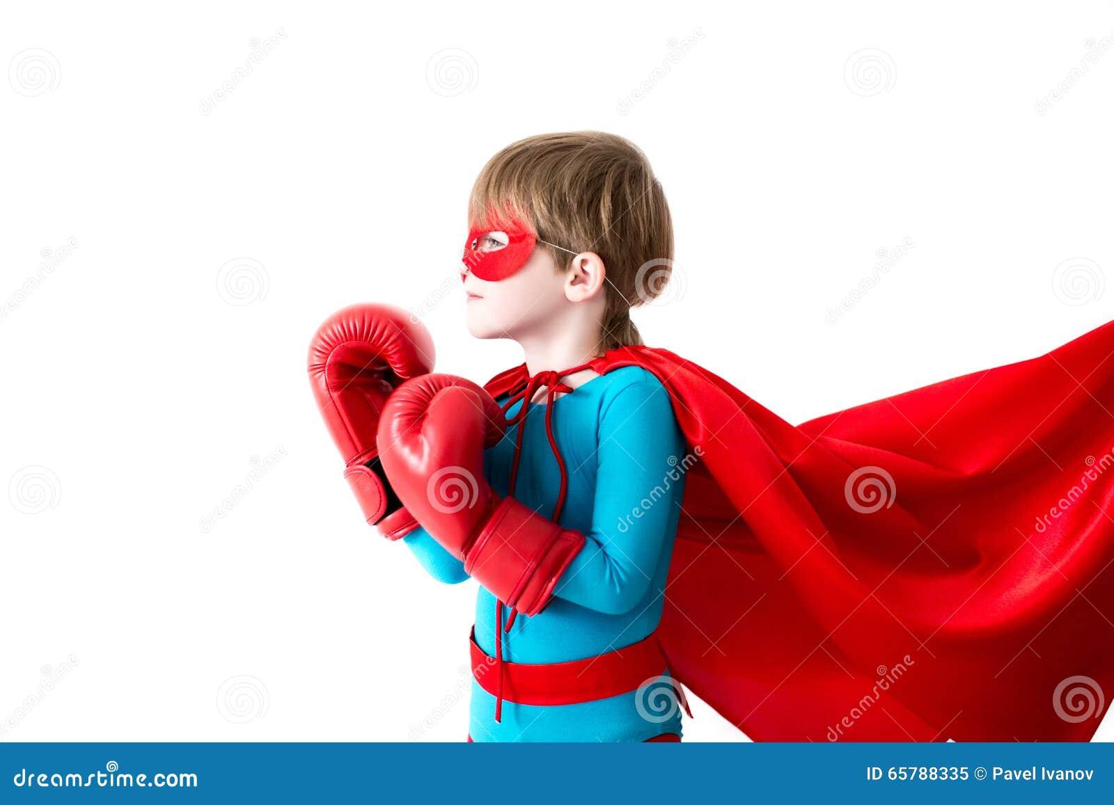 Rapaz pequeno em luvas de encaixotamento e super-herói do terno isolado em um fundo branco