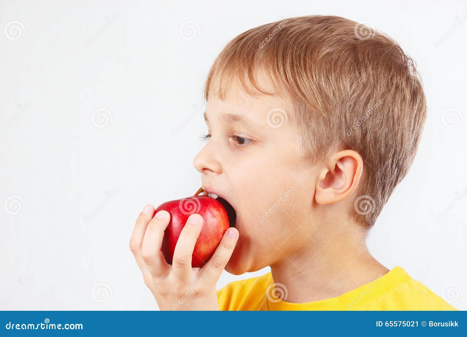 Rapaz pequeno em uma camisa amarela que come a maçã vermelha