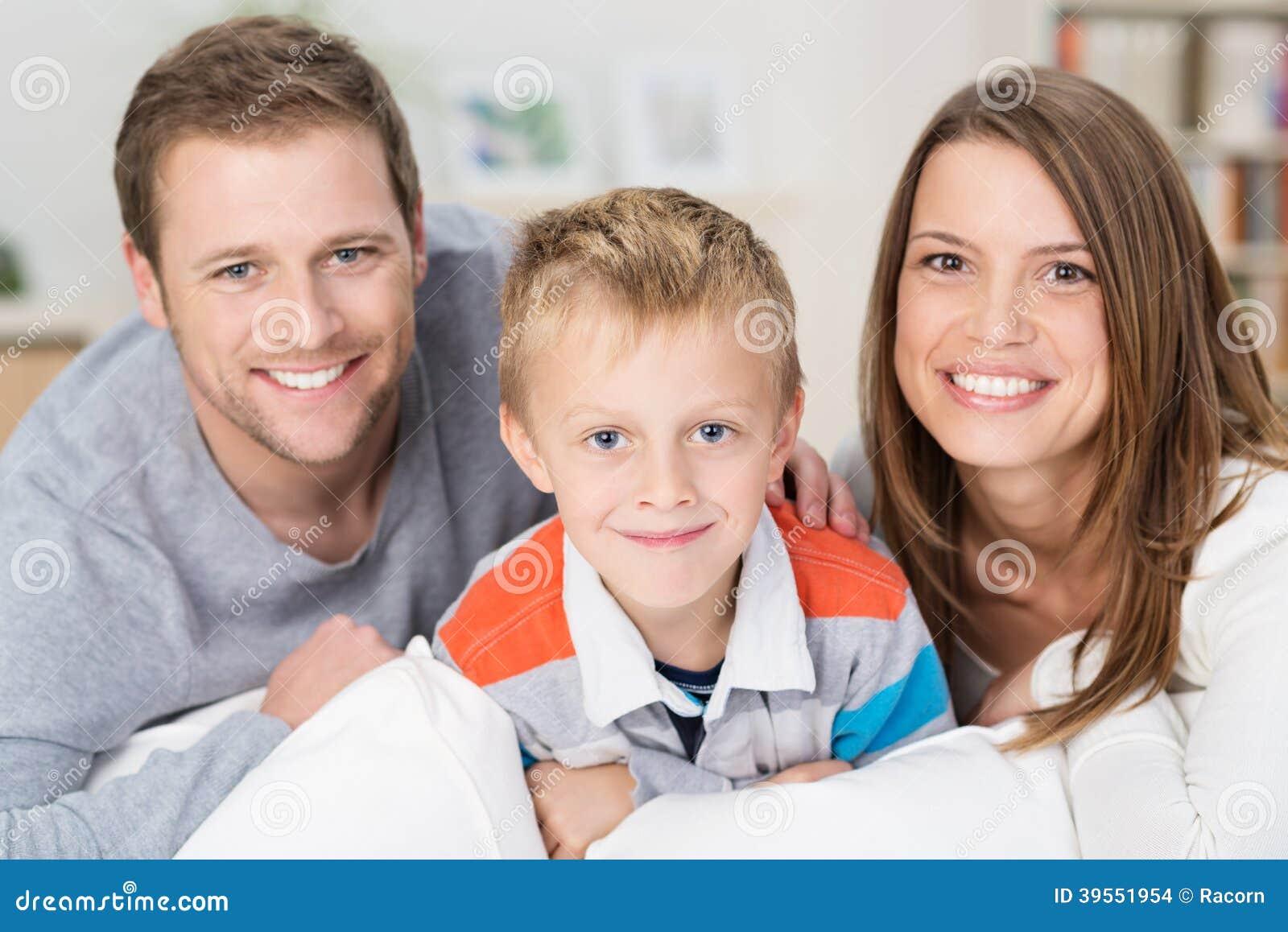 Rapaz pequeno feliz com seus pais novos de sorriso