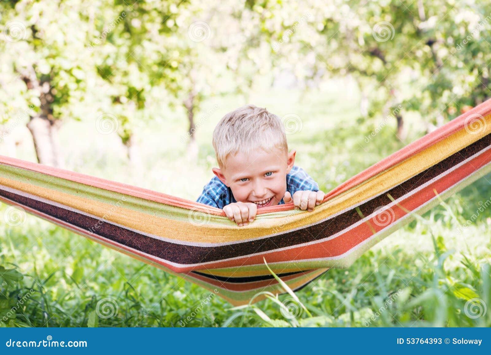 Rapaz pequeno feliz na rede do jogo no jardim do verão