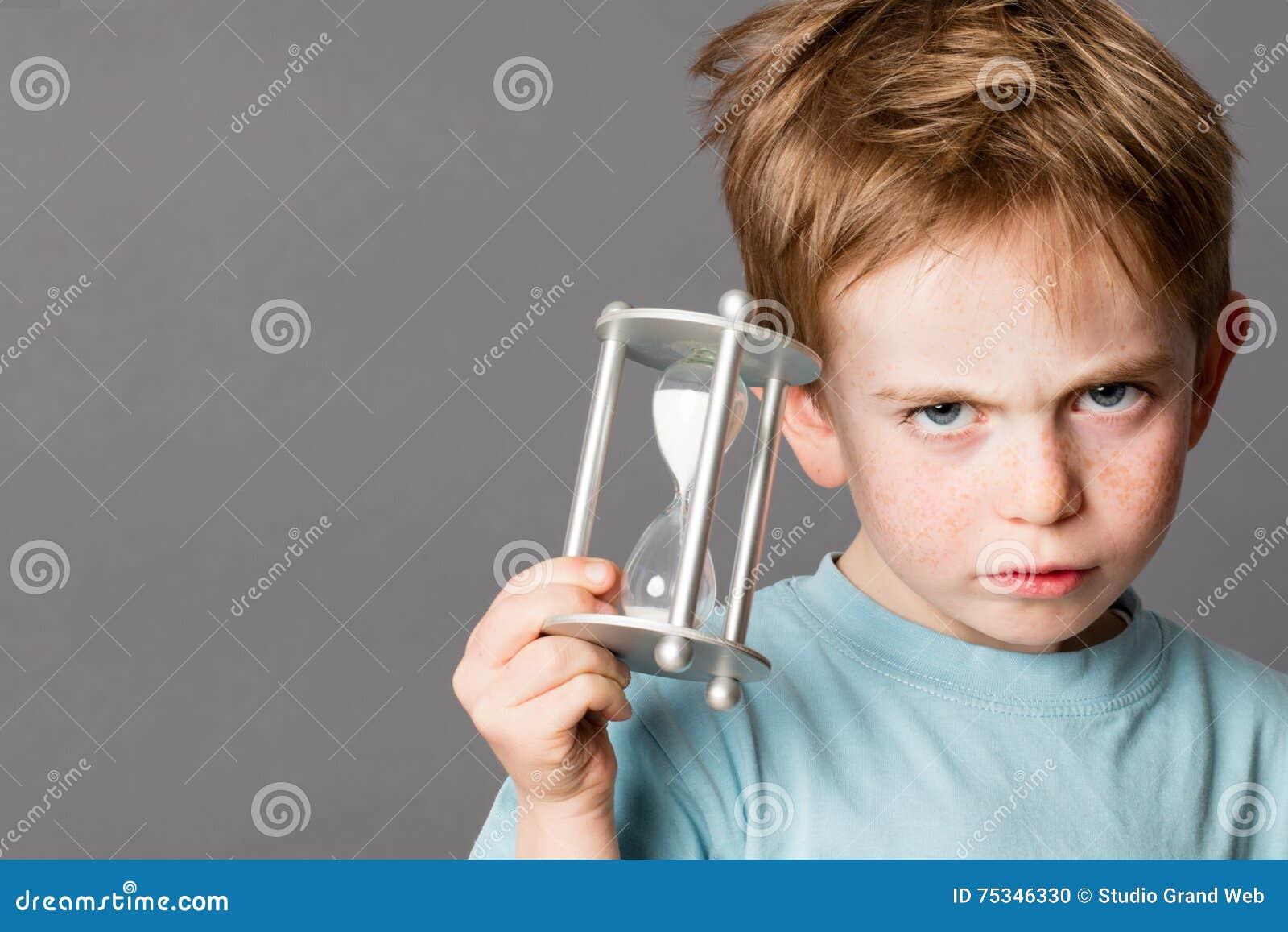 Rapaz pequeno infeliz com um temporizador do ovo para o conceito do tempo