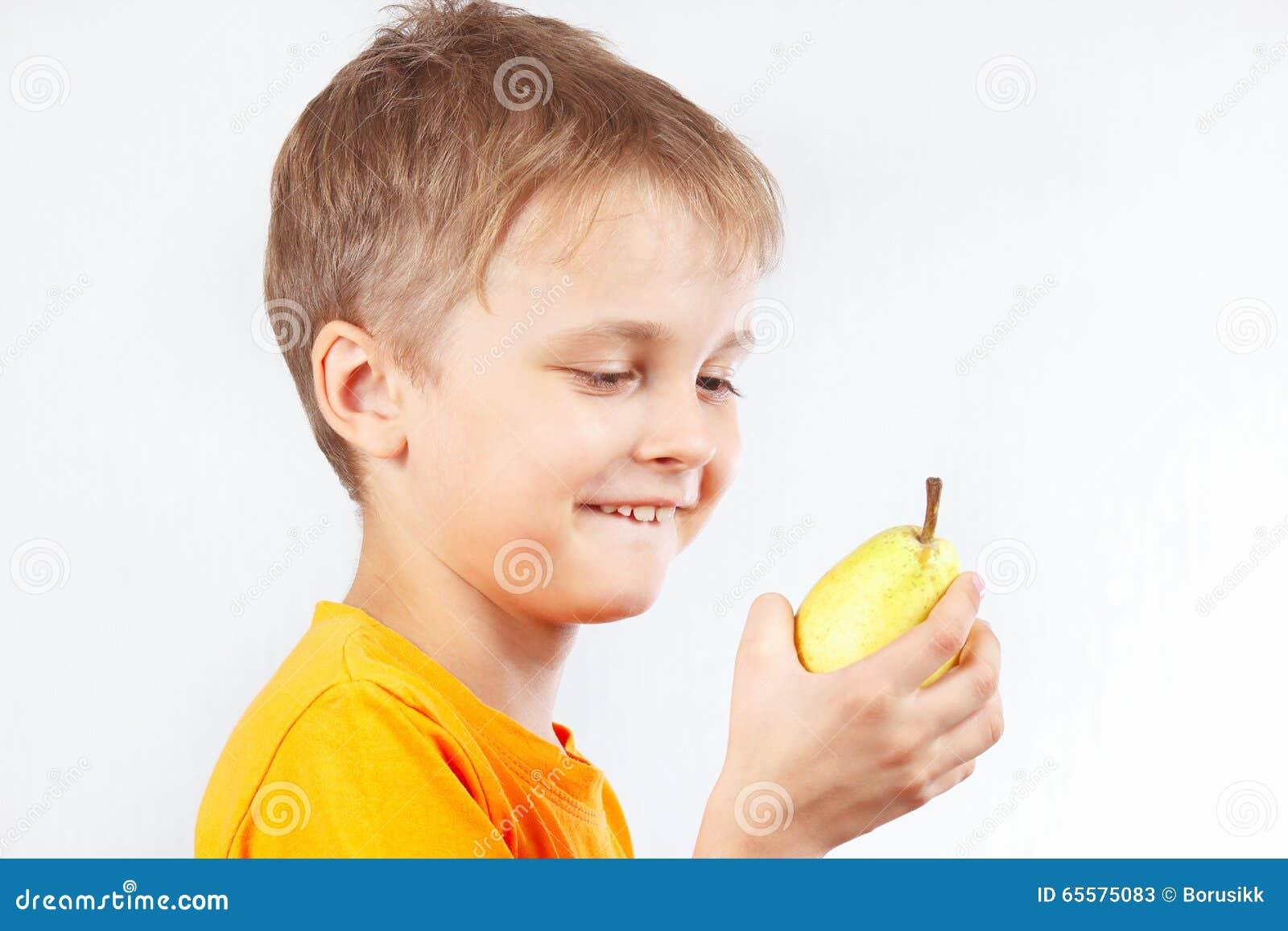 Rapaz pequeno na camisa alaranjada com a pera amarela madura