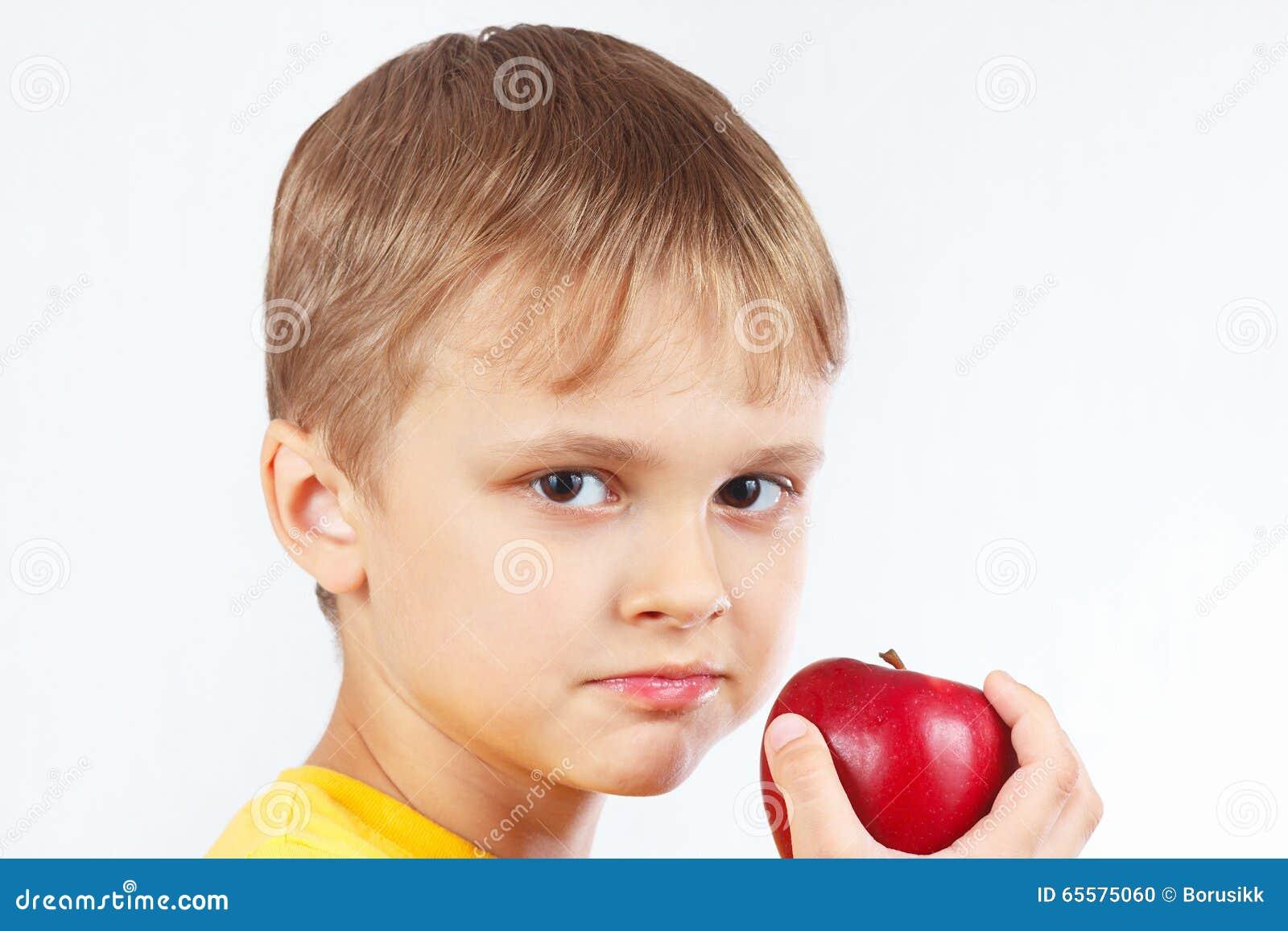 Rapaz pequeno na camisa amarela com a maçã vermelha madura