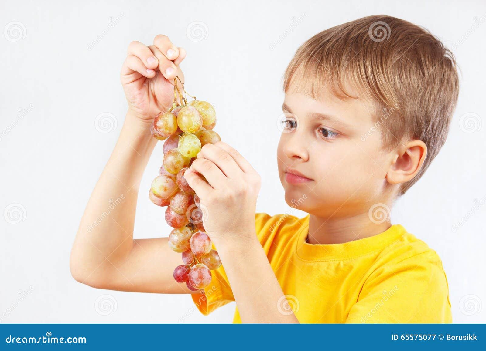 Rapaz pequeno na camisa amarela que come uma uva madura