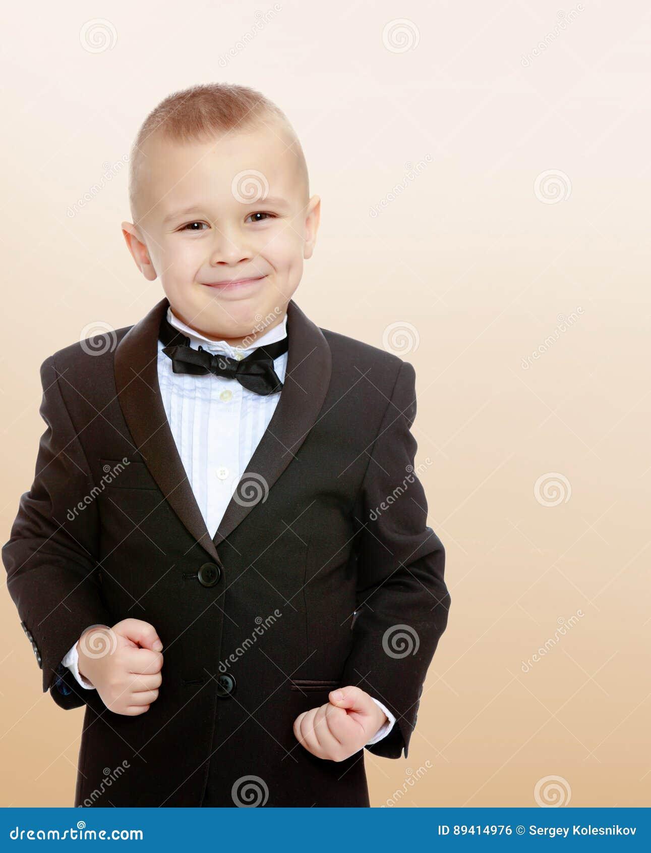 Rapaz pequeno na moda em um terno preto com um laço