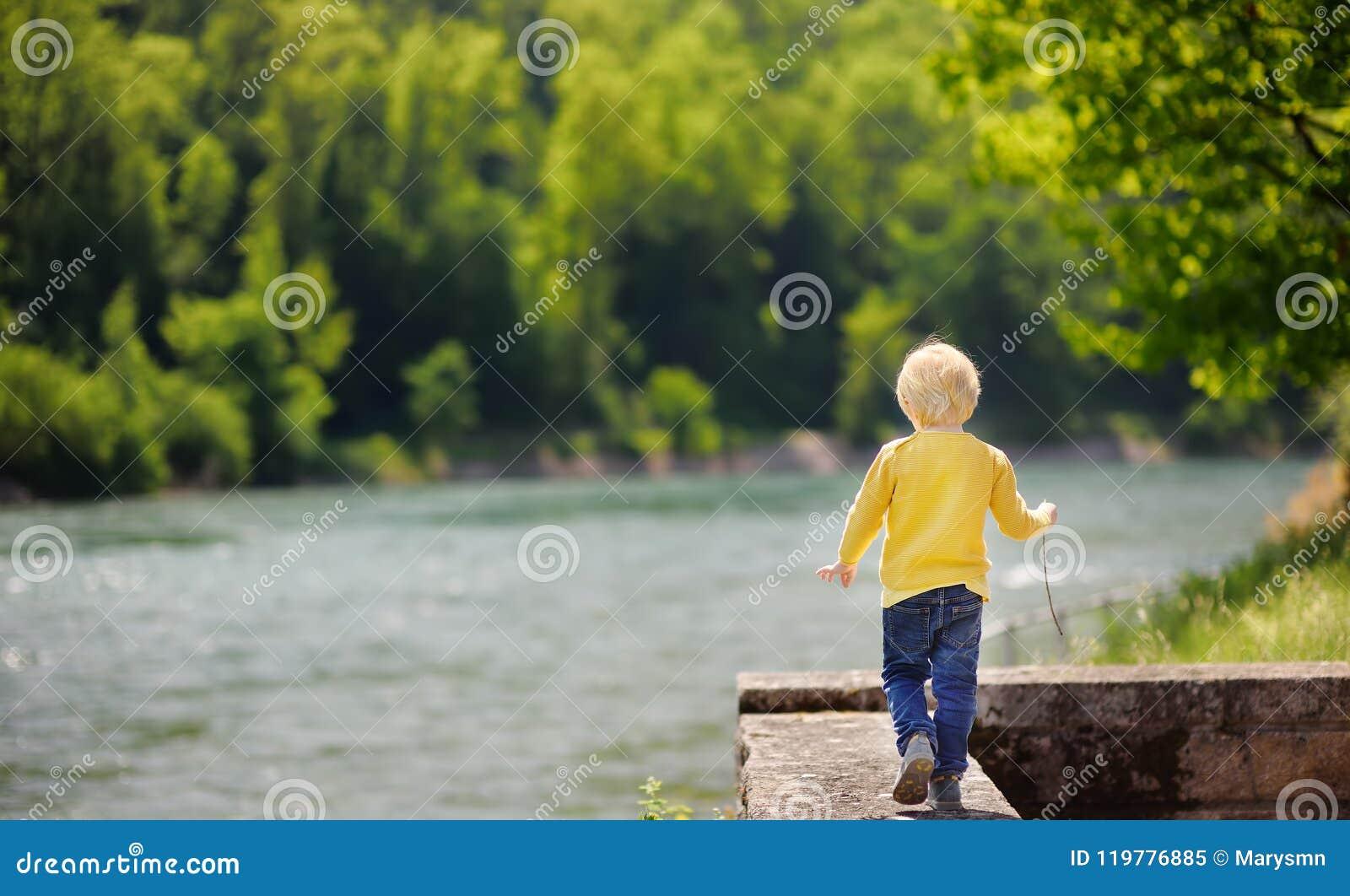 Rapaz pequeno na situação perigosa durante a caminhada no parque