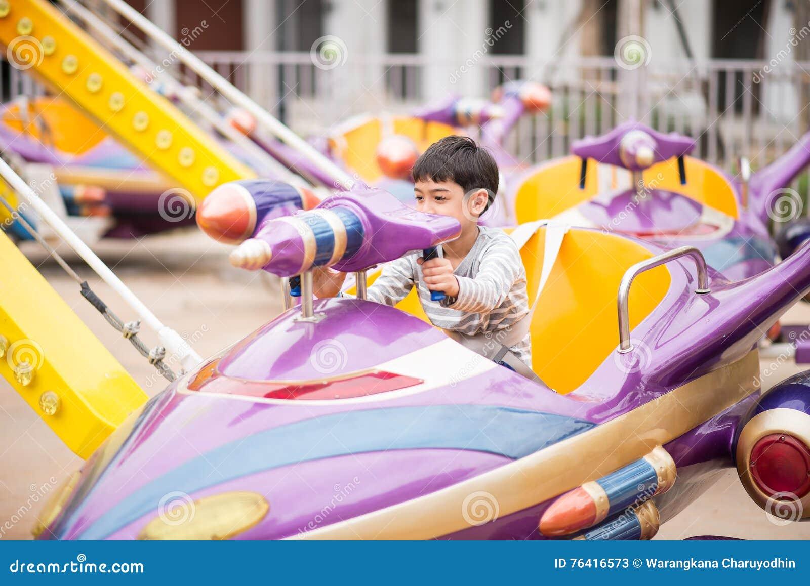 Rapaz pequeno no parque de diversões exterior