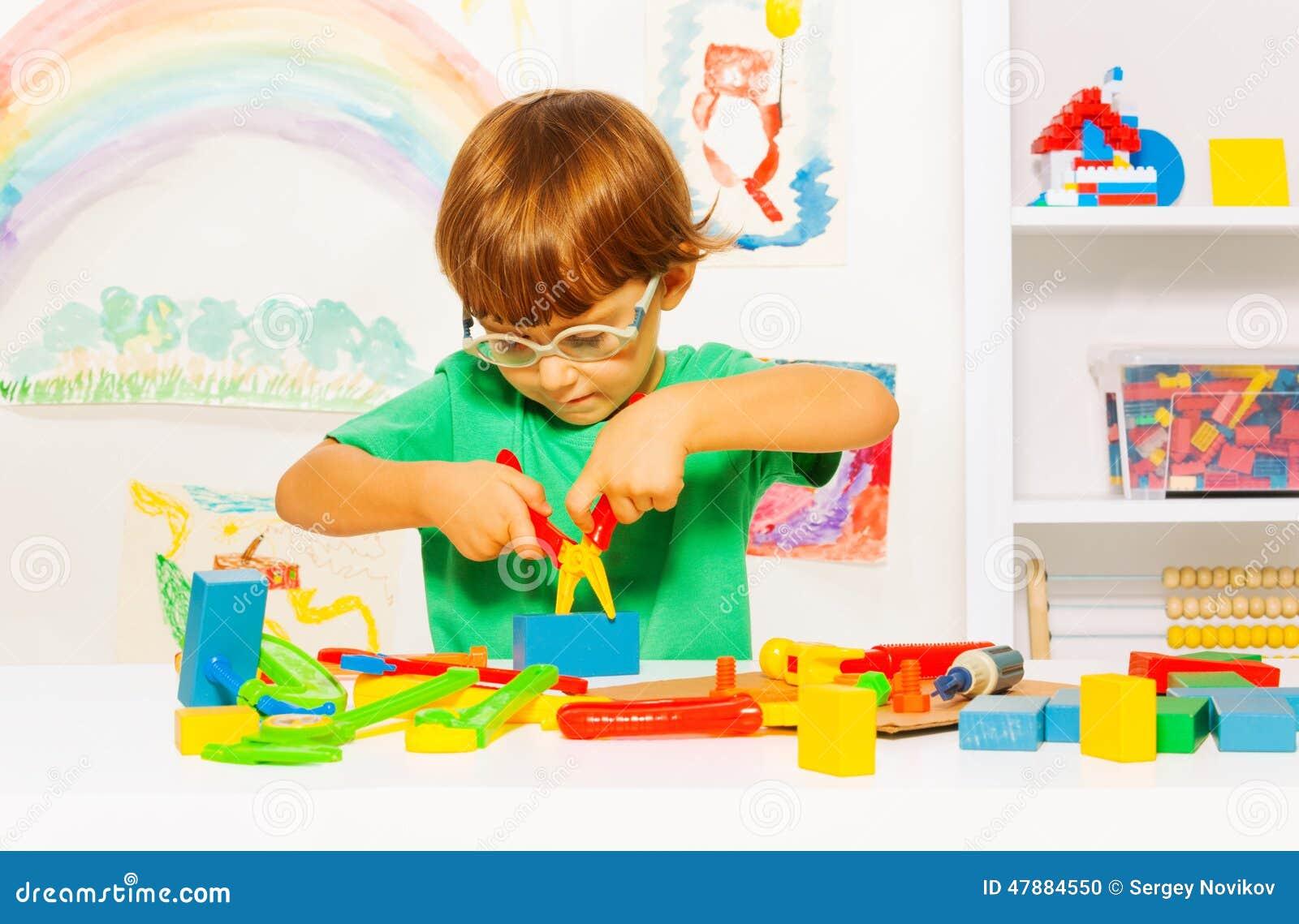 Rapaz pequeno nos vidros que aprende usar alicates