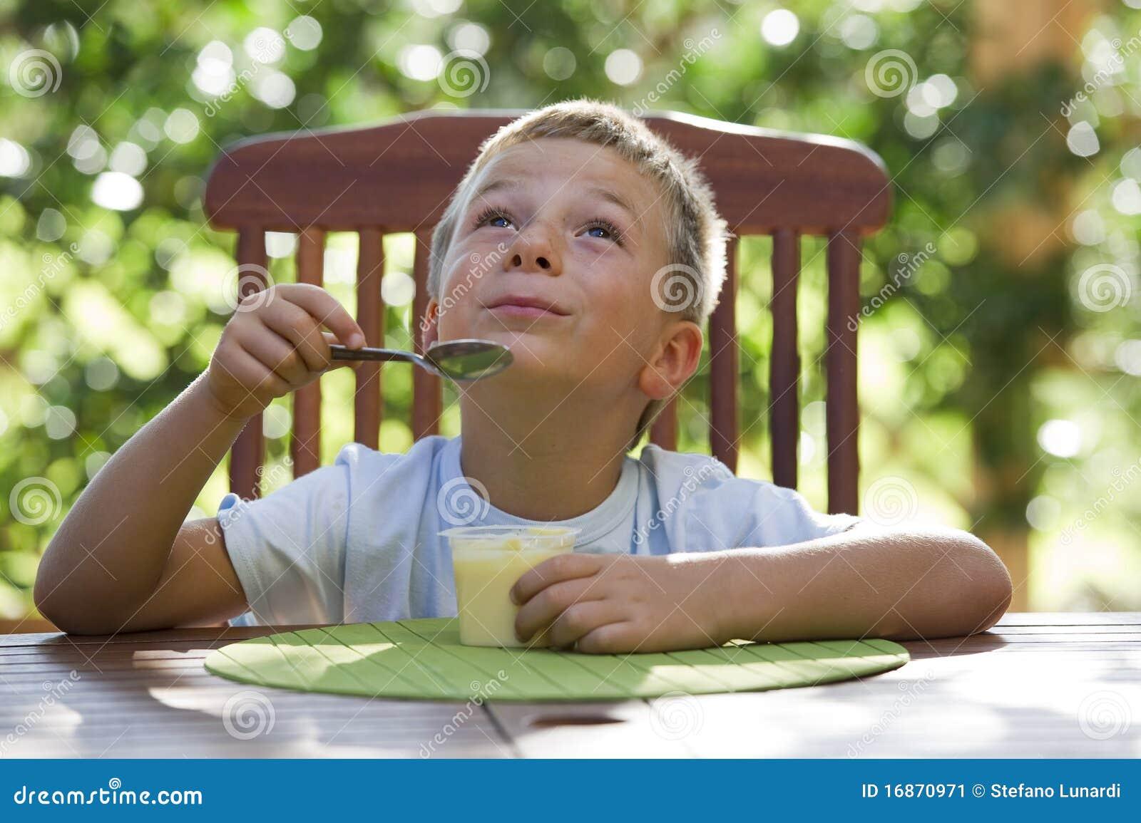 Rapaz pequeno que come o pudim