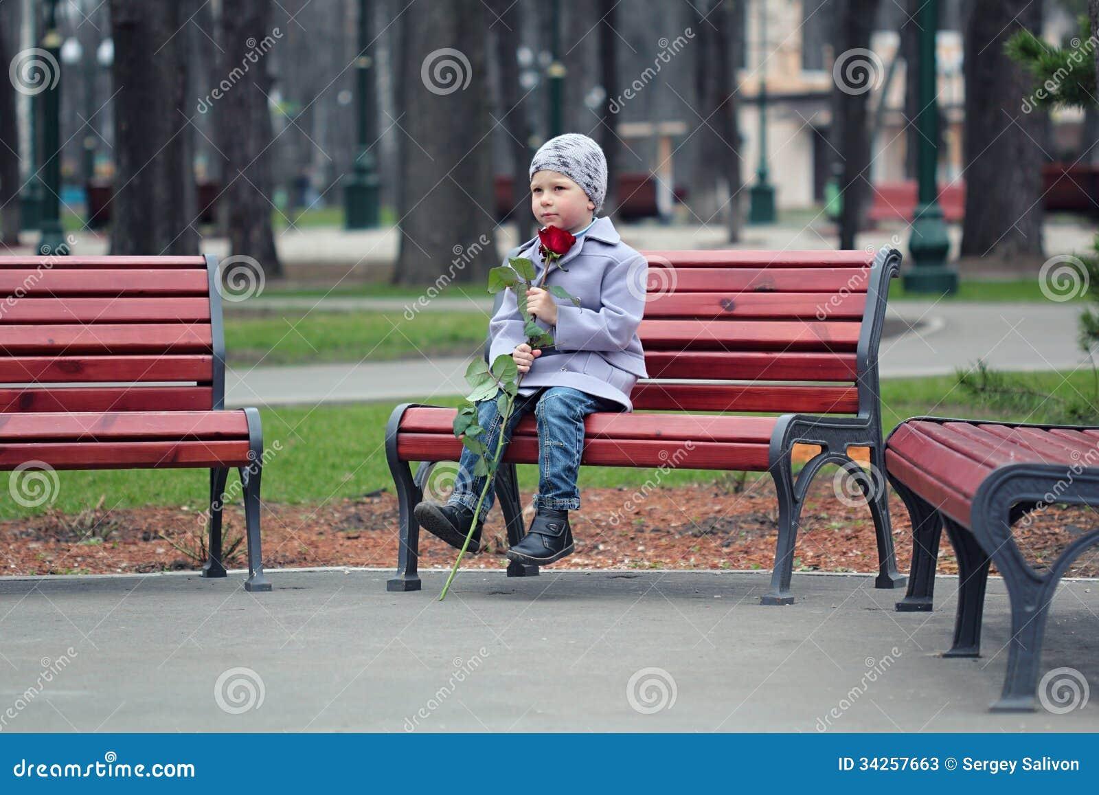 Rapaz pequeno que espera no parque