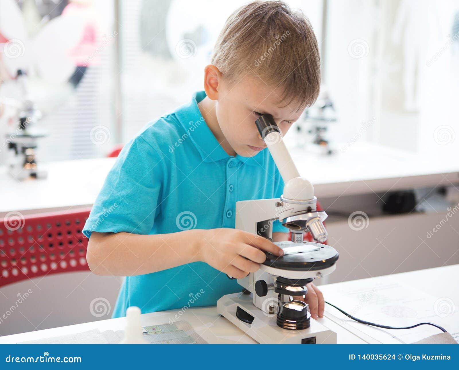 Rapaz pequeno que faz a pesquisa da bioquímica no laboratório Um menino da aparência europeia em um polo conduz experiências biol