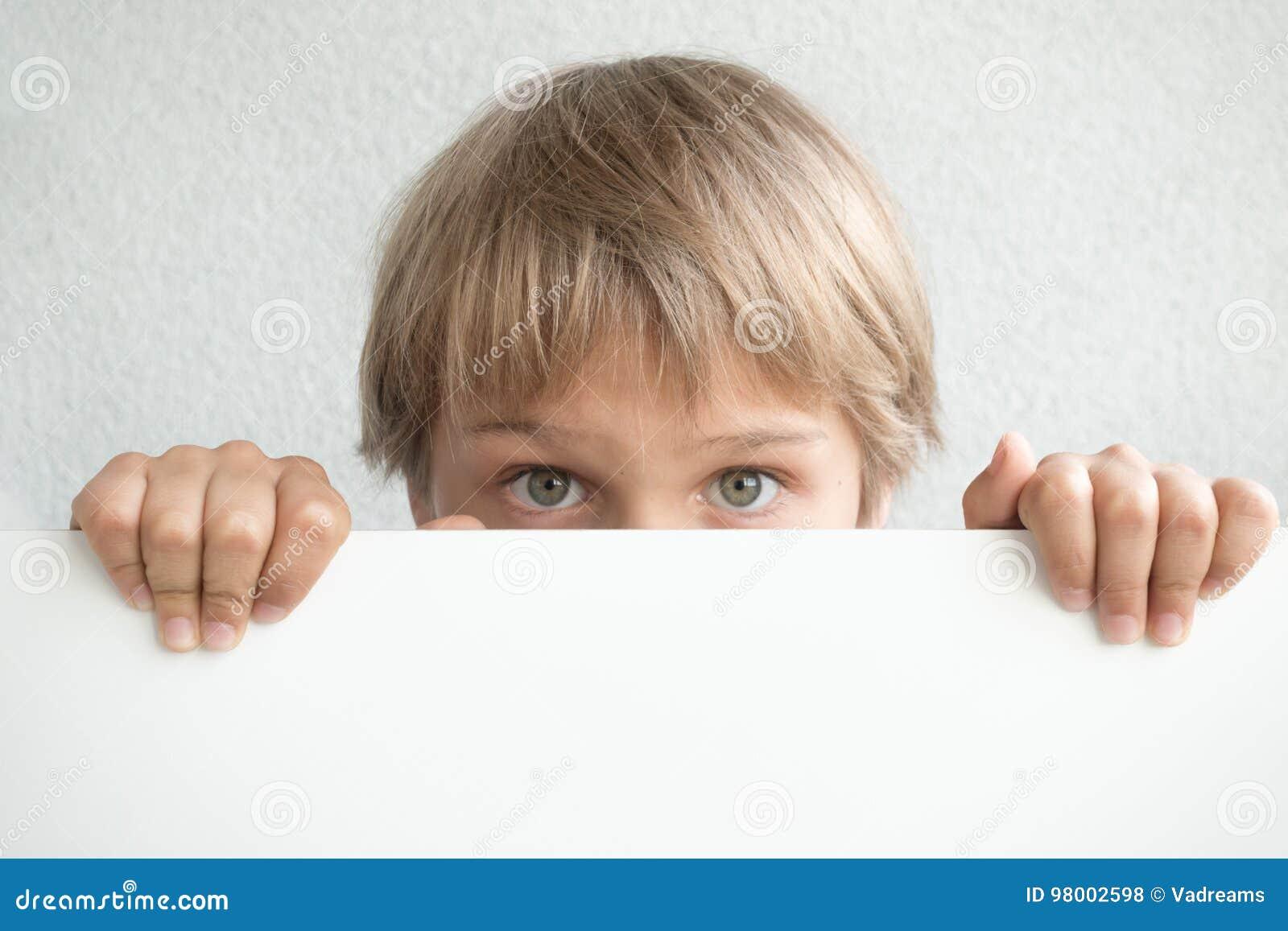 Rapaz pequeno que guardam o sinal branco vazio ou cartaz que esconde sua cara