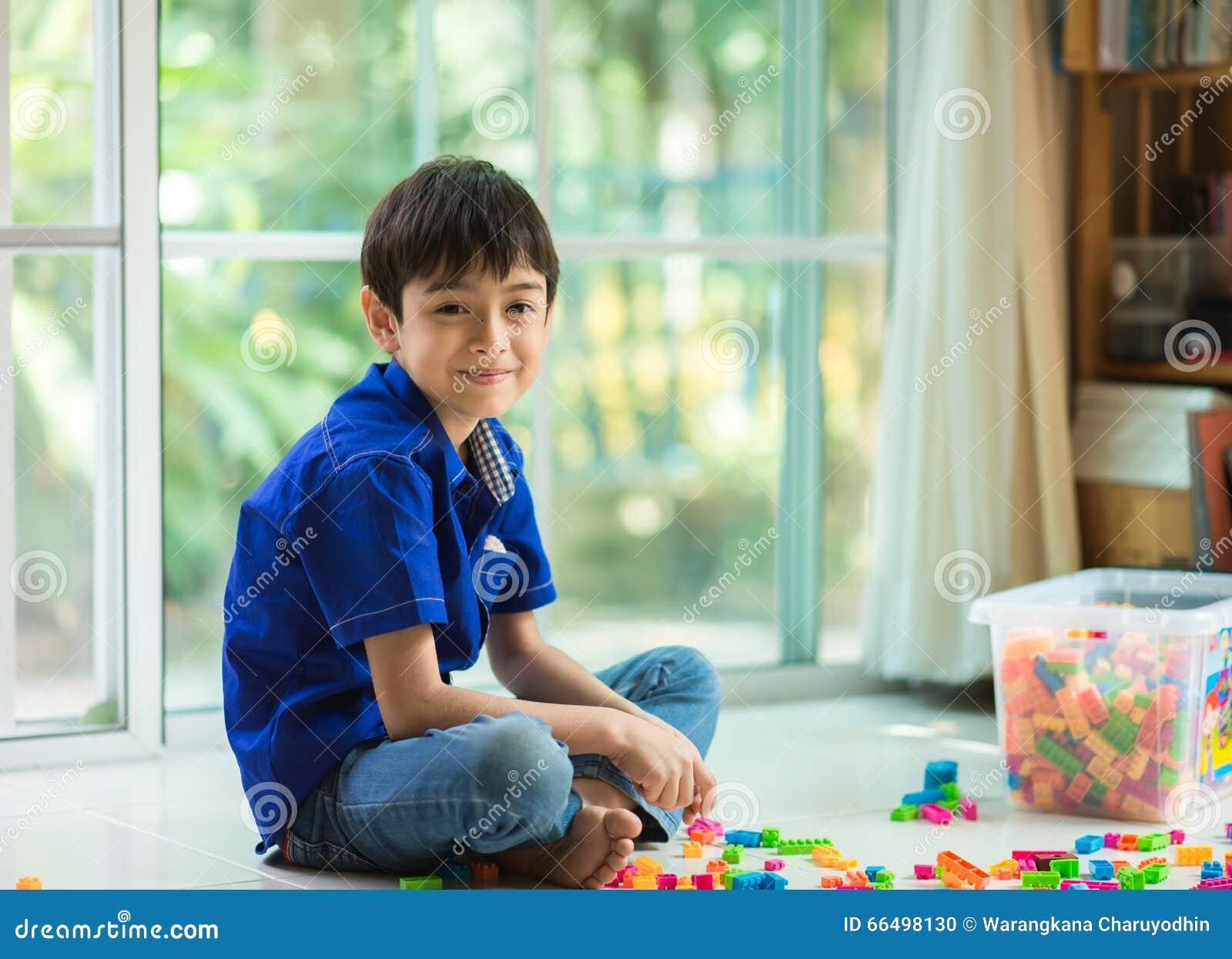 Rapaz pequeno que joga a casa interna do bloco