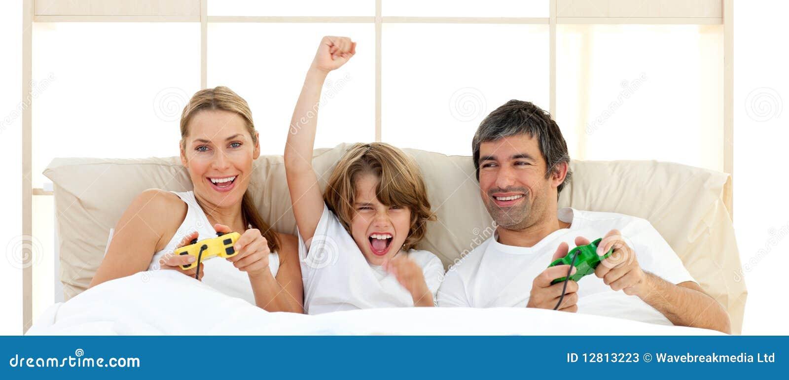 Rapaz pequeno que joga o jogo video com sua família