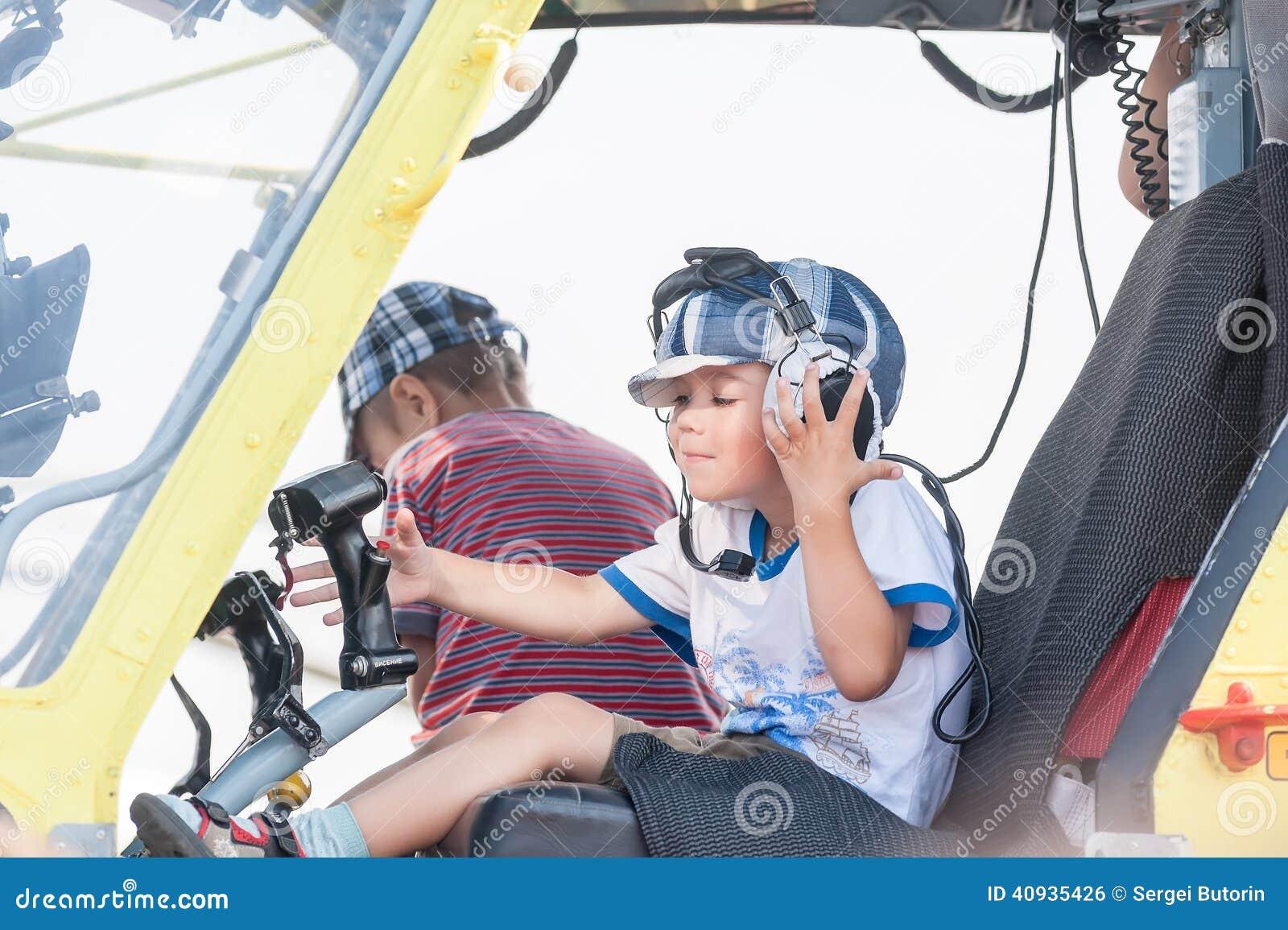 Rapaz pequeno que senta-se na cabine do helicóptero MI-8