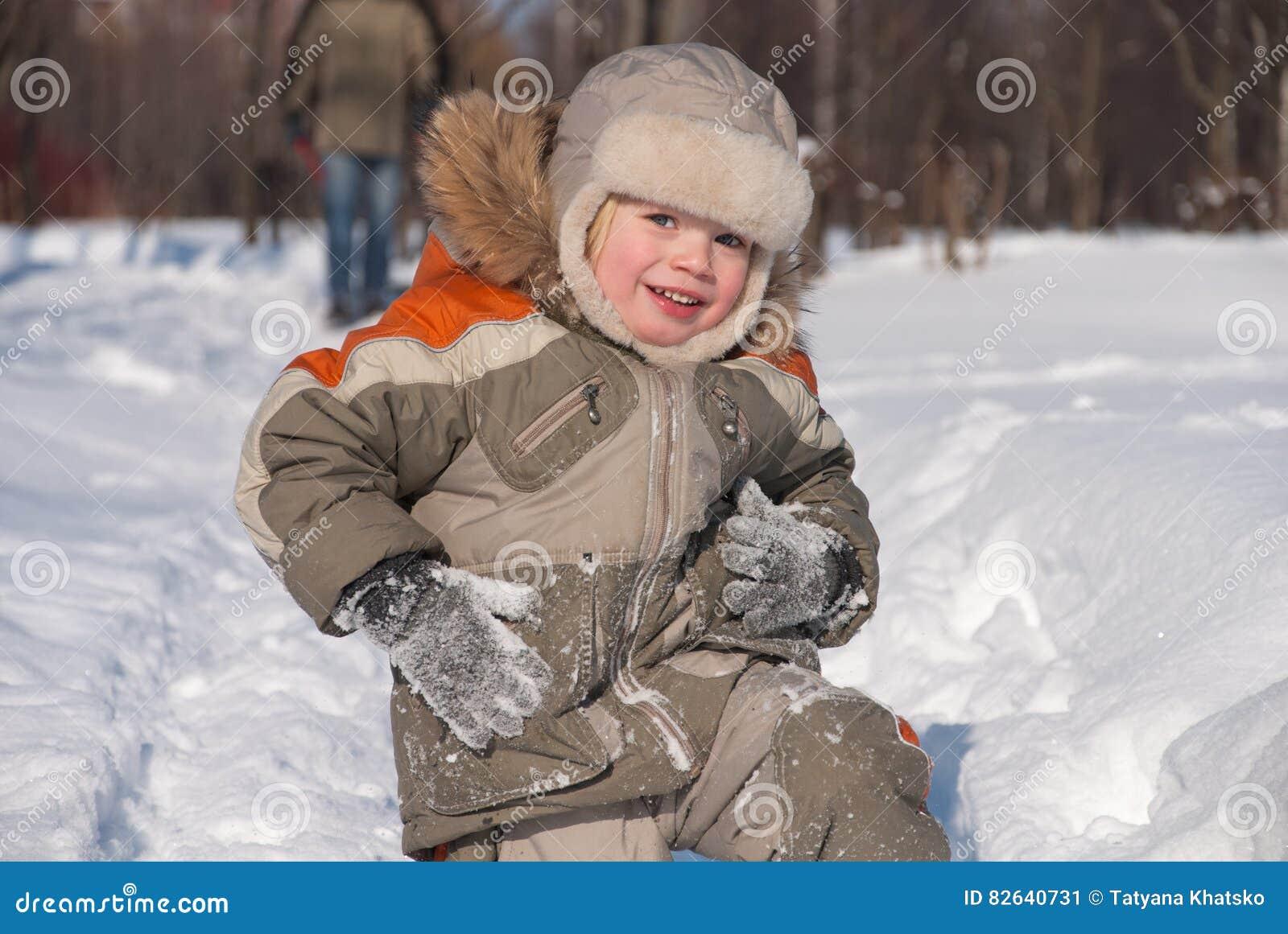 Rapaz pequeno que tem o divertimento na neve
