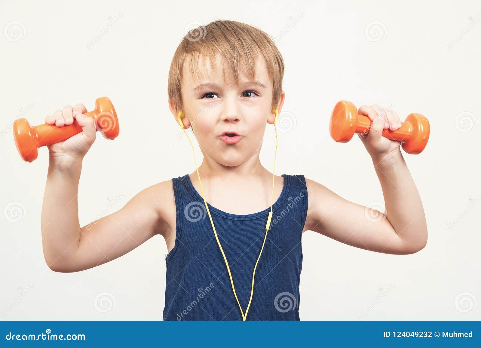 Rapaz pequeno saudável que dá certo com pesos sobre o fundo branco Estilo de vida, esportes das crianças e infância saudáveis Men