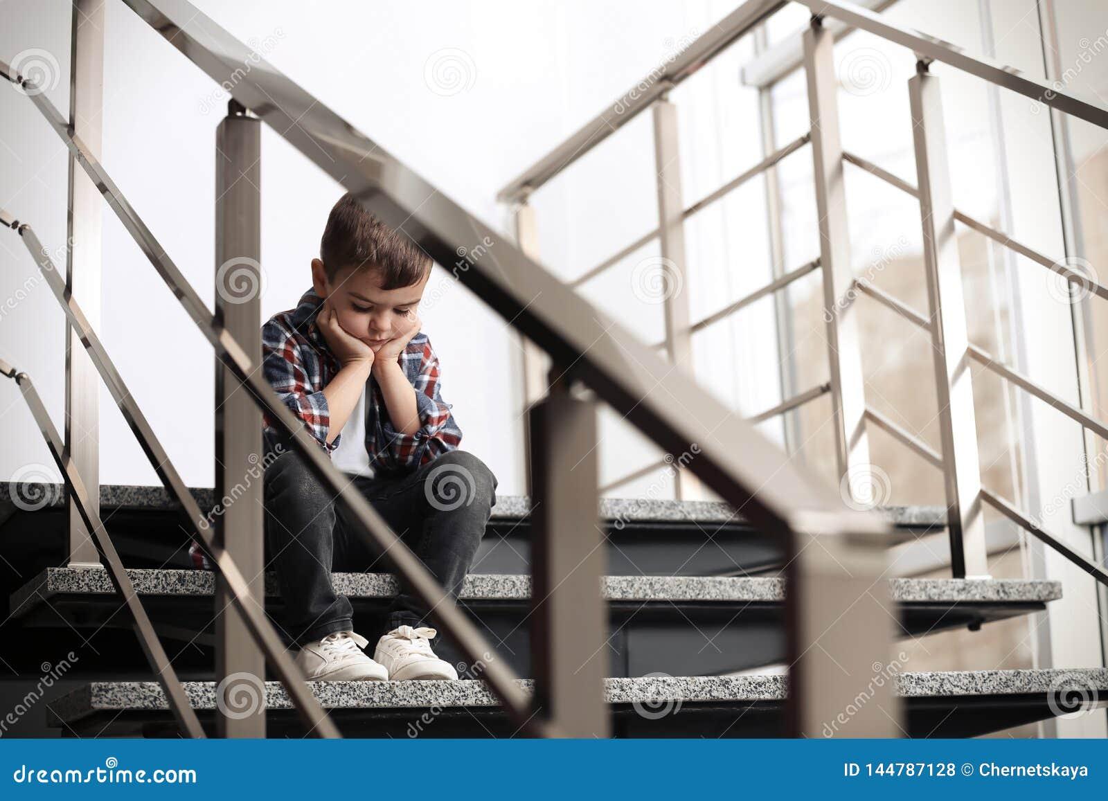 Rapaz pequeno triste que senta-se em escadas