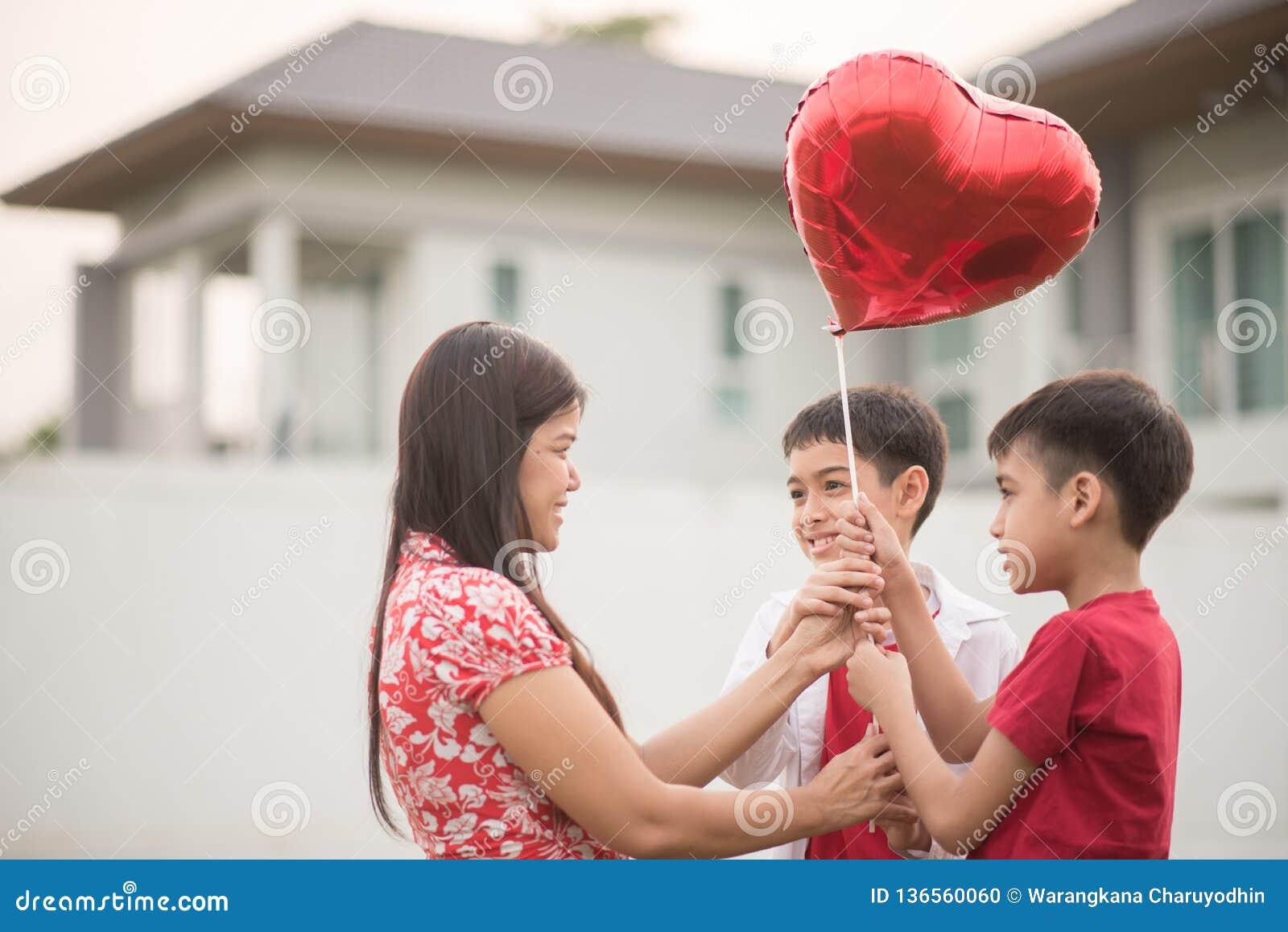 Rapazes pequenos que dão o coração do balão a seu amor de mãe